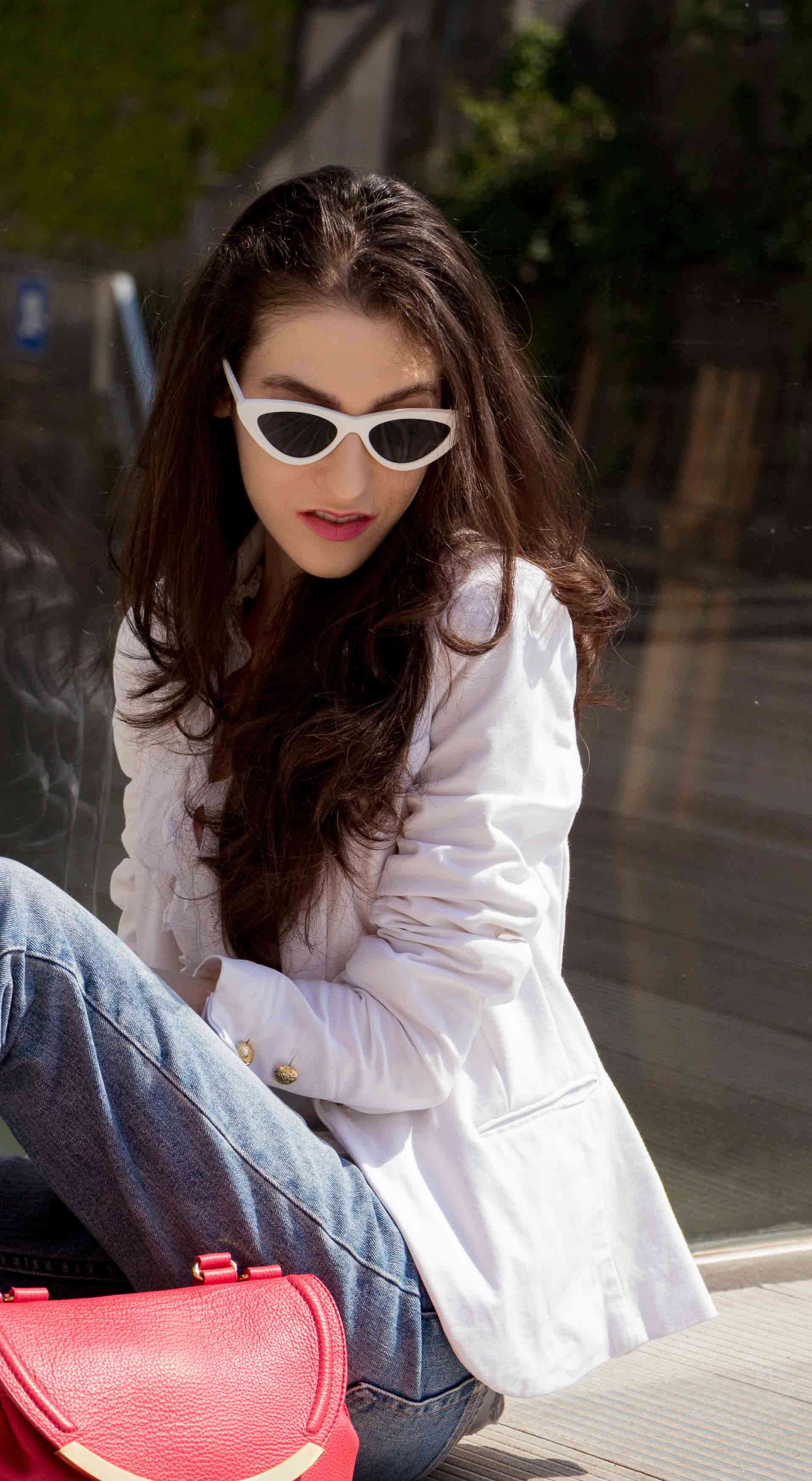 Veronika Lipar Fashion Blogger of Brunette from Wall Street dressed in white mules, blue A.P.C. mom jeans, white fringe blouse, white blazer, pink gloves, pink top handle bag and Le Specs Lolita white cat eye sunglasses while sitting on the floor on the bridge