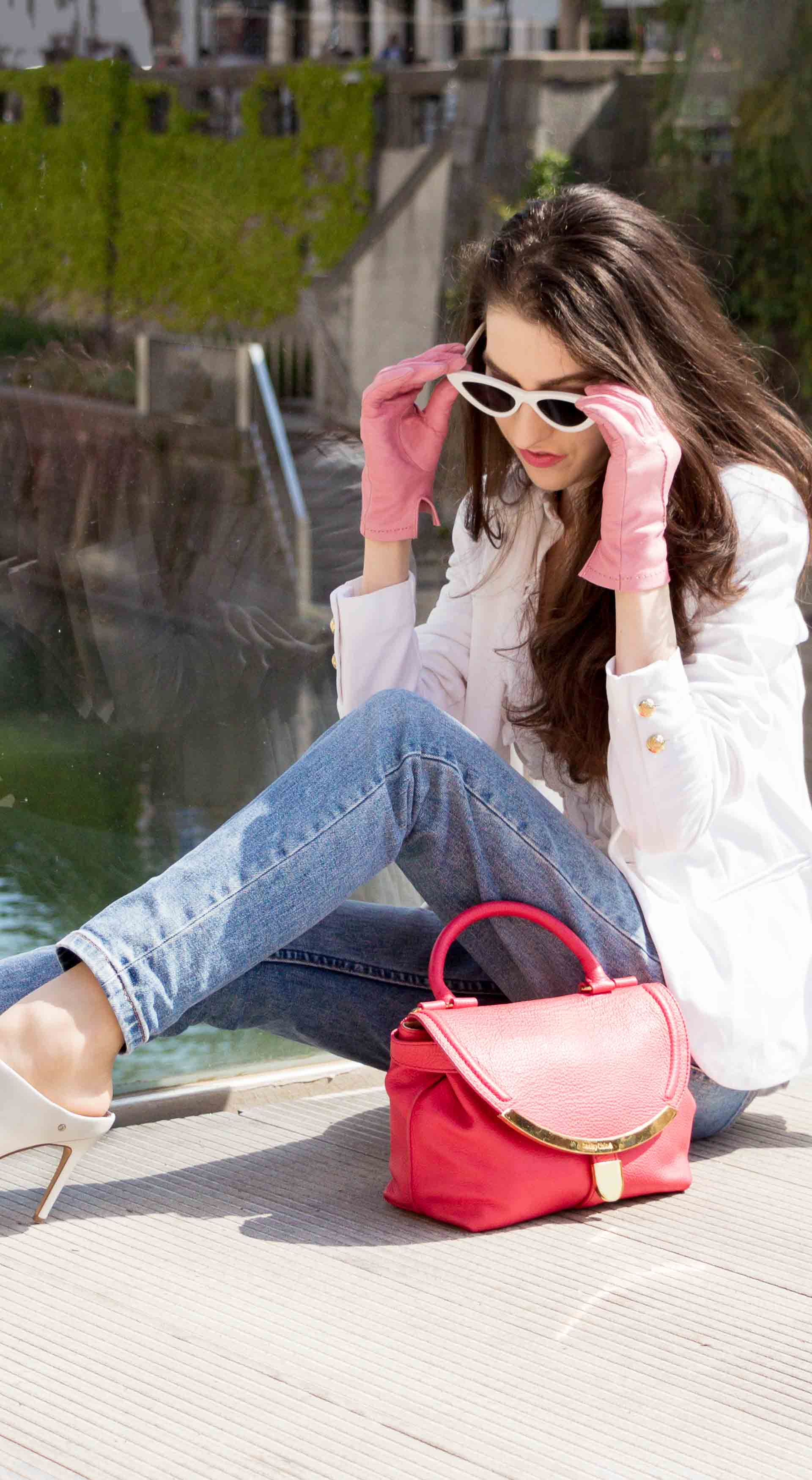 Veronika Lipar Fashion Blogger of Brunette from Wall Street wearing white mules, blue A.P.C. mom jeans, white fringe blouse, white blazer, pink gloves, pink top handle bag and Le Specs Lolita white cat eye sunglasses while sitting on the floor on the bridge