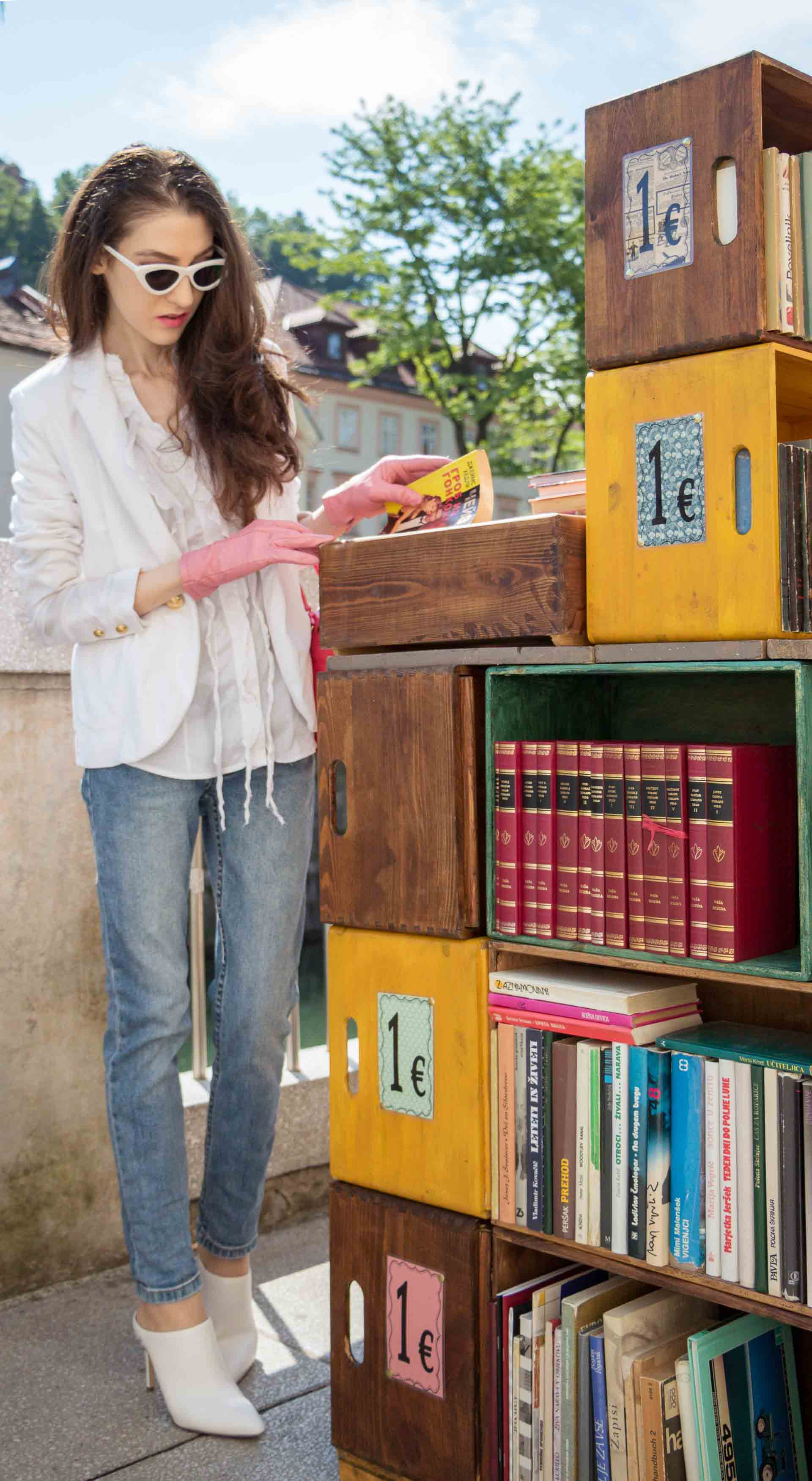 Veronika Lipar Fashion Blogger of Brunette from Wall Street wearing white mules, blue A.P.C. mom jeans, white fringe blouse, white blazer, pink gloves, pink top handle bag and Le Specs Lolita white cat eye sunglasses while choosing a book at the book stand on the street
