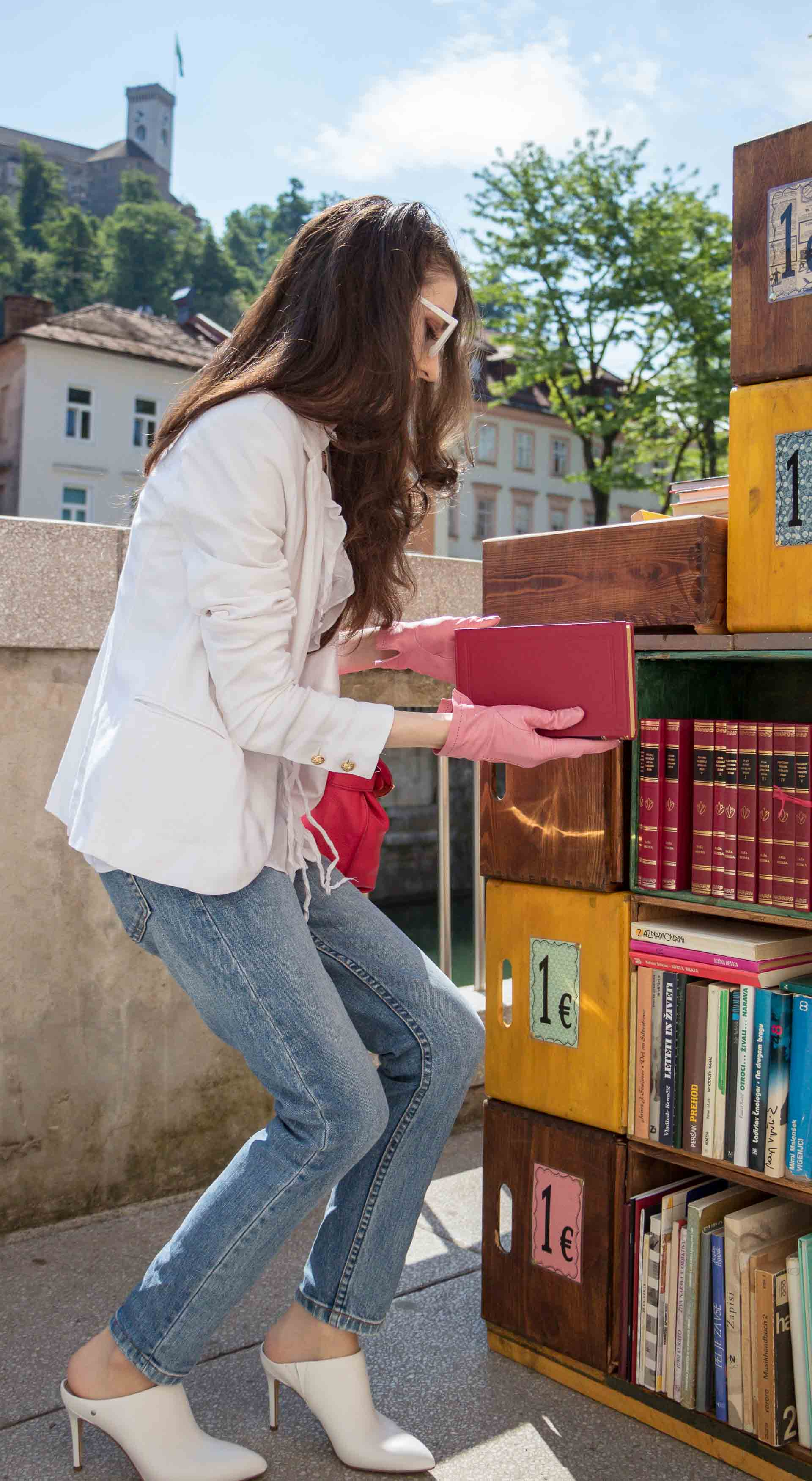 Veronika Lipar Fashion Blogger of Brunette from Wall Street dressed in white mules, blue A.P.C. mom jeans, white fringe blouse, white blazer, pink gloves, pink top handle bag and Le Specs Lolita white cat eye sunglasses while choosing a book at the book stand on the street
