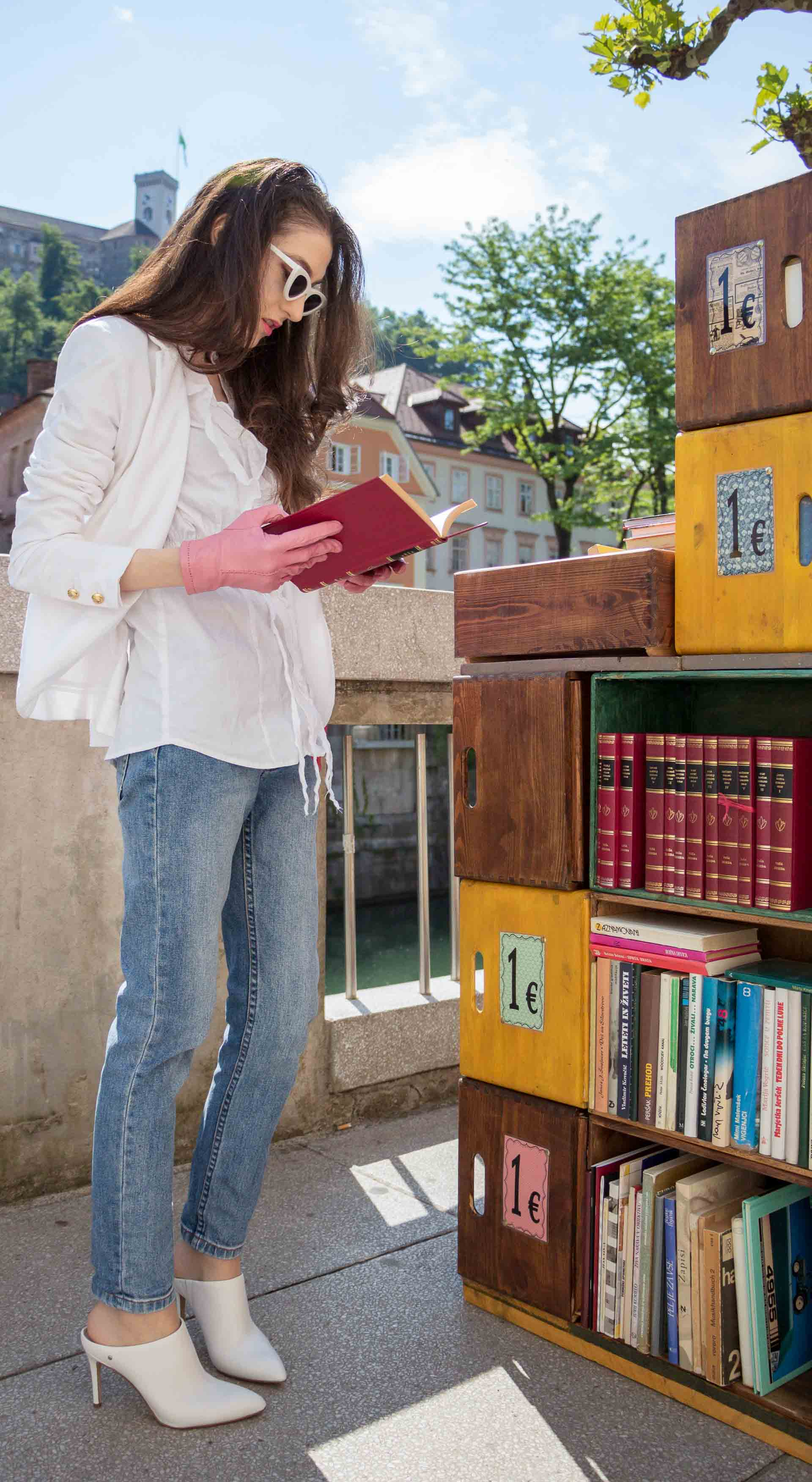 Veronika Lipar Fashion Blogger of Brunette from Wall Street wearing white mules, blue A.P.C. mom jeans, white fringe blouse, white blazer, pink gloves, pink top handle bag and Le Specs Lolita white cat eye sunglasses while reading book on the street