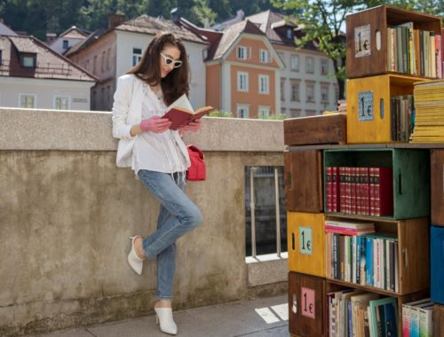 Veronika Lipar Fashion Blogger of Brunette from Wall Street wearing white mules, blue A.P.C. mom jeans, white fringe blouse, white blazer, pink gloves, pink top handle bag and Le Specs Lolita white cat eye sunglasses while leaning on the wall and reading book on the street