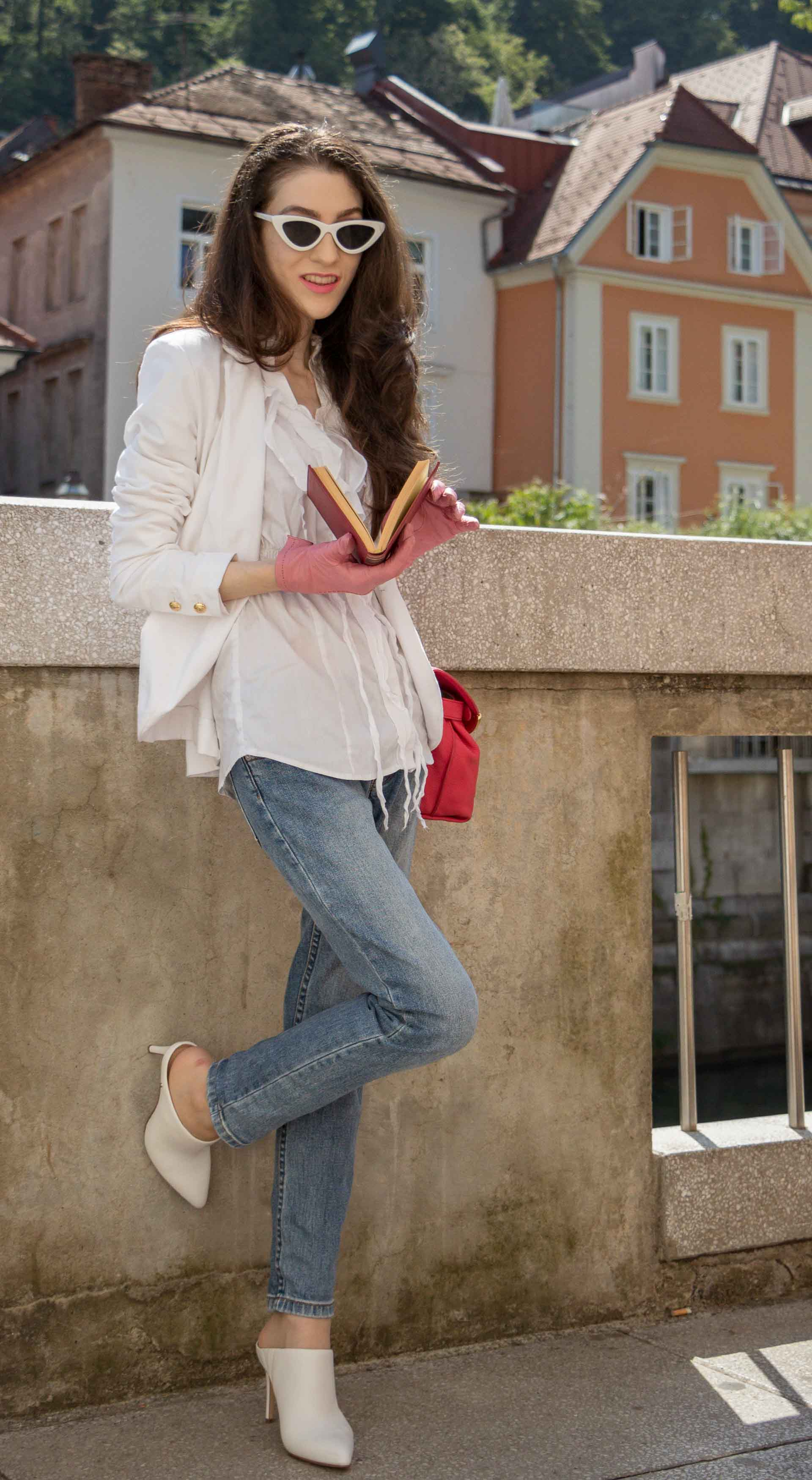 Veronika Lipar Fashion Blogger of Brunette from Wall Street dressed in white mules, blue A.P.C. mom jeans, white fringe blouse, white blazer, pink gloves, pink top handle bag and Le Specs Lolita white cat eye sunglasses while leaning on the wall and reading book on the street