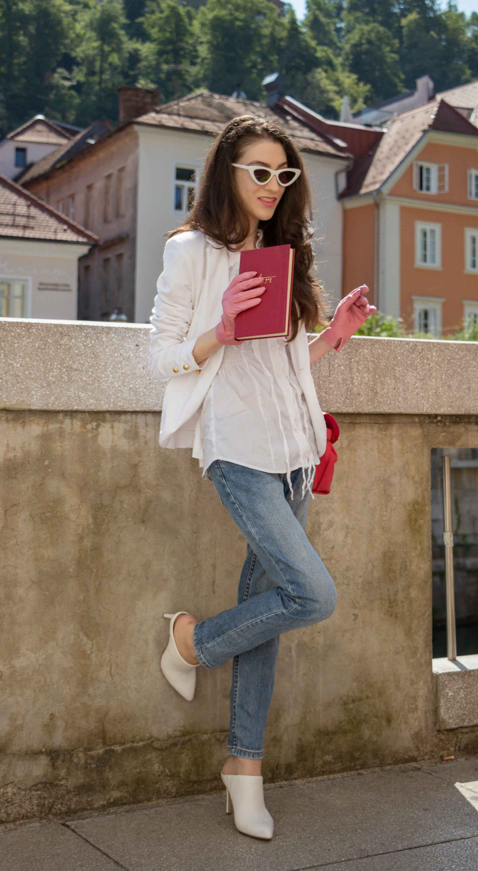 Veronika Lipar Fashion Blogger of Brunette from Wall Street dressed in white mules, blue A.P.C. mom jeans, white fringe blouse, white blazer, pink gloves, pink top handle bag and Le Specs Lolita white cat eye sunglasses while reading book by the book stand on the street