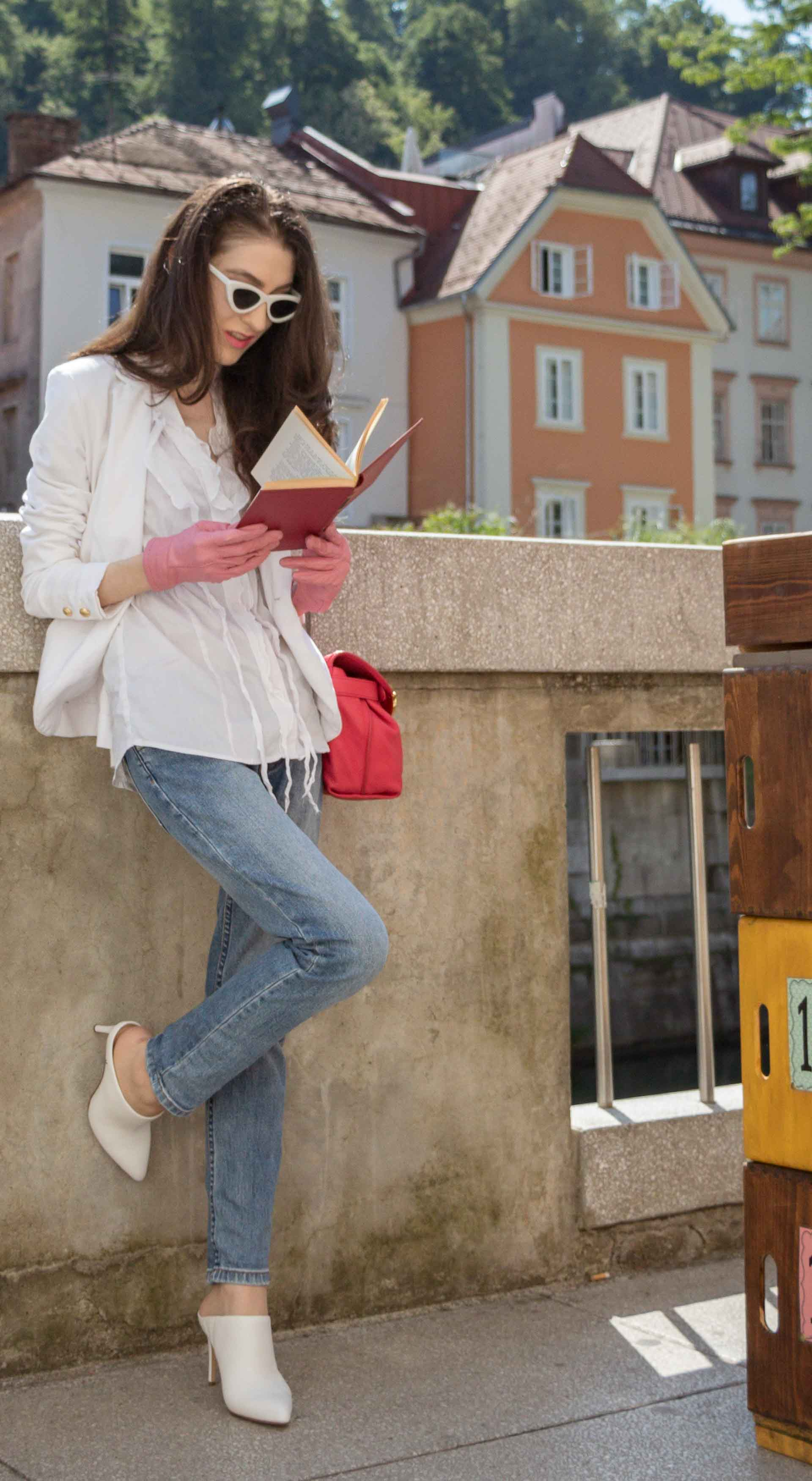 Veronika Lipar Fashion Blogger of Brunette from Wall Street wearing white mules, blue A.P.C. mom jeans, white fringe blouse, white blazer, pink gloves, pink top handle bag and Le Specs Lolita white cat eye sunglasses while reading book by the book stand on the street