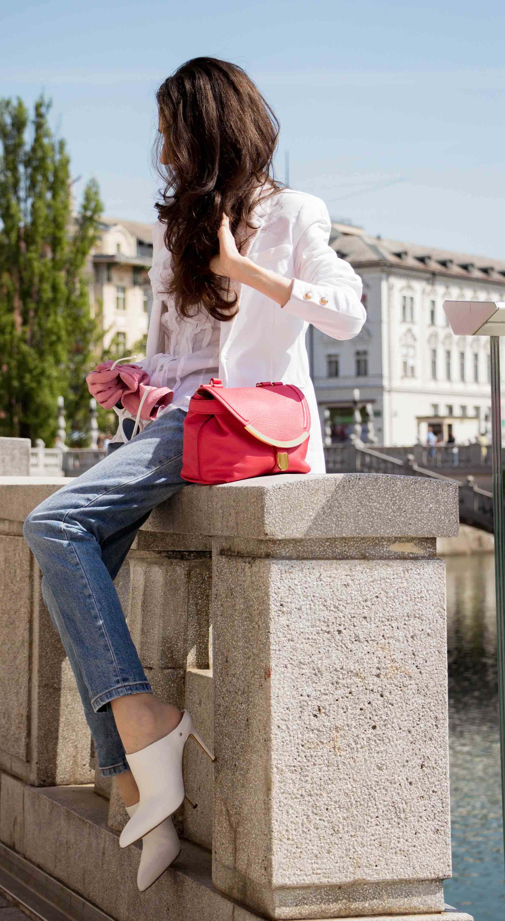 Veronika Lipar Fashion Blogger of Brunette from Wall Street wearing white mules, blue A.P.C. mom jeans, white fringe blouse, white blazer, pink gloves, pink top handle bag and Le Specs Lolita white cat eye sunglasses while sitting on the wall touching hair