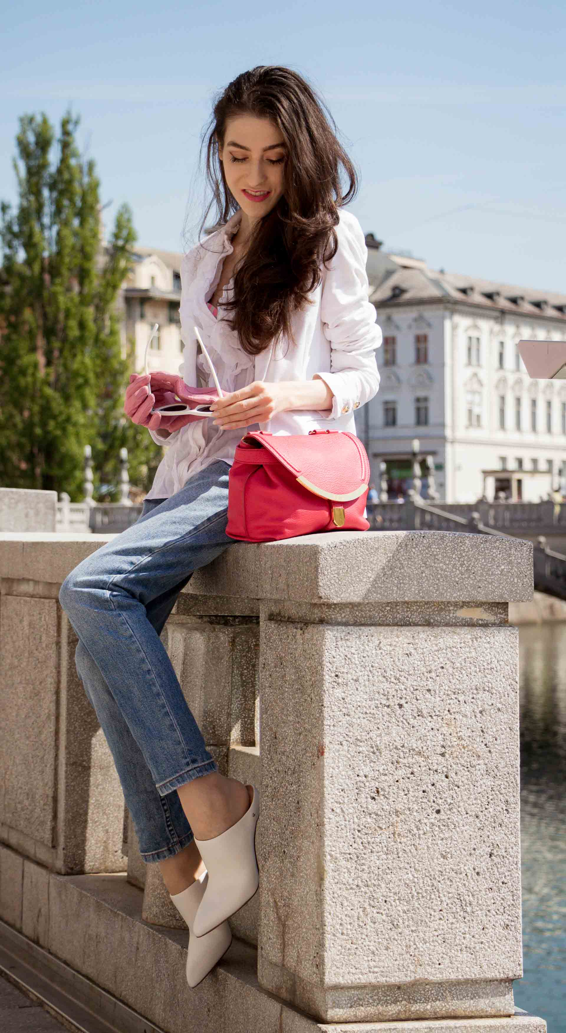 Veronika Lipar Fashion Blogger of Brunette from Wall Street dressed in white mules, blue A.P.C. mom jeans, white fringe blouse, white blazer, pink gloves, pink top handle bag and Le Specs Lolita white cat eye sunglasses while sitting on the wall