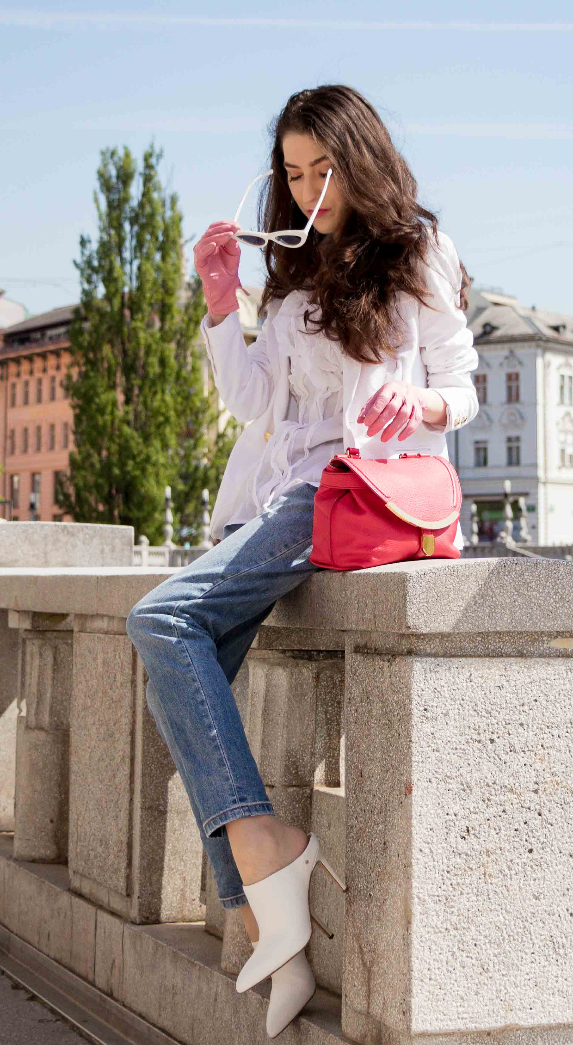 Veronika Lipar Fashion Blogger of Brunette from Wall Street wearing white mules, blue A.P.C. mom jeans, white fringe blouse, white blazer, pink gloves, pink top handle bag and Le Specs Lolita white cat eye sunglasses while sitting on the wall