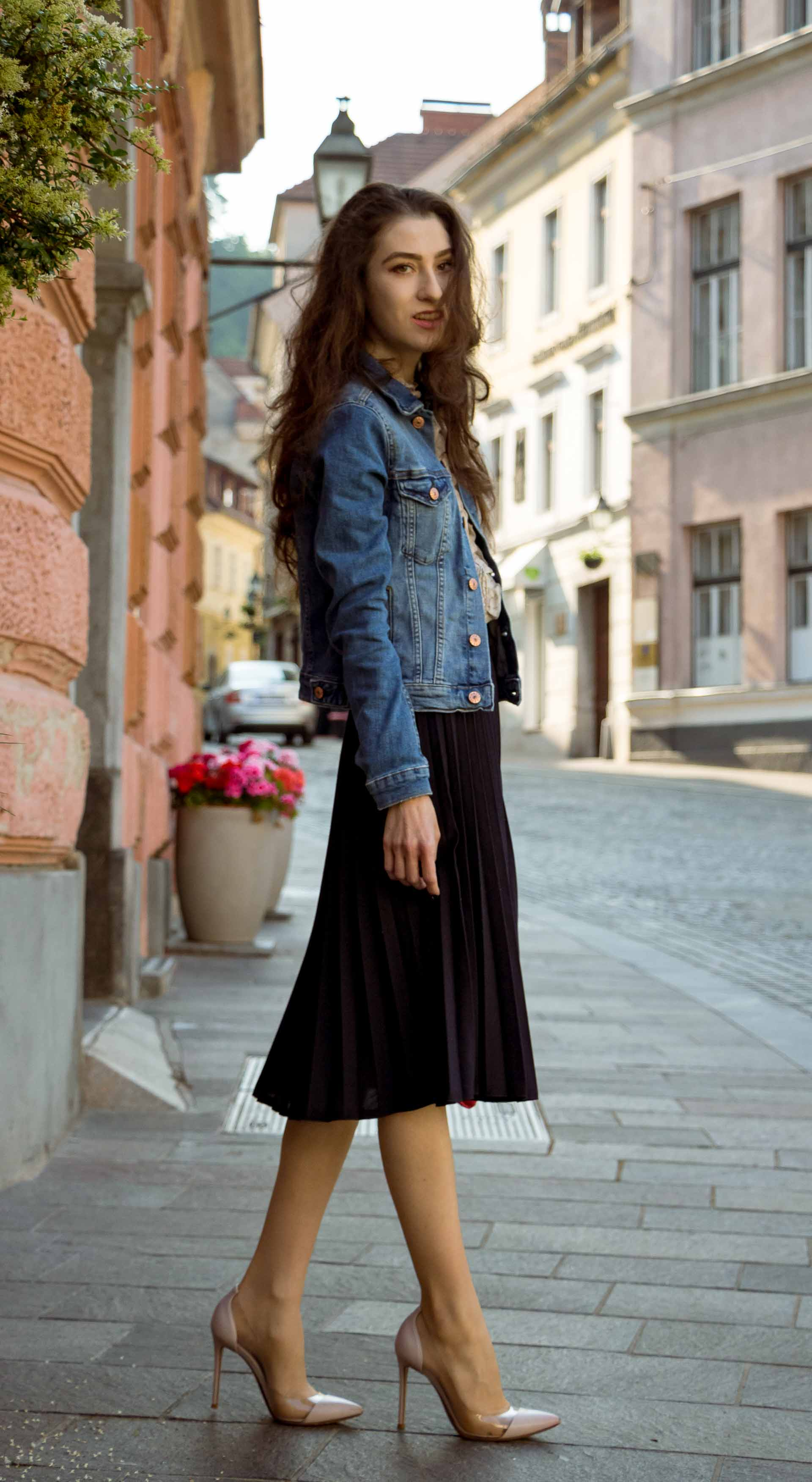 Veronika Lipar Fashion Blogger of Brunette from Wall Street wearing H&M denim jacket, floral blouse, midi pleated skirt, Gianvito Rossi plexi pumps, pink top handle bag while standing on the street in Ljubljana