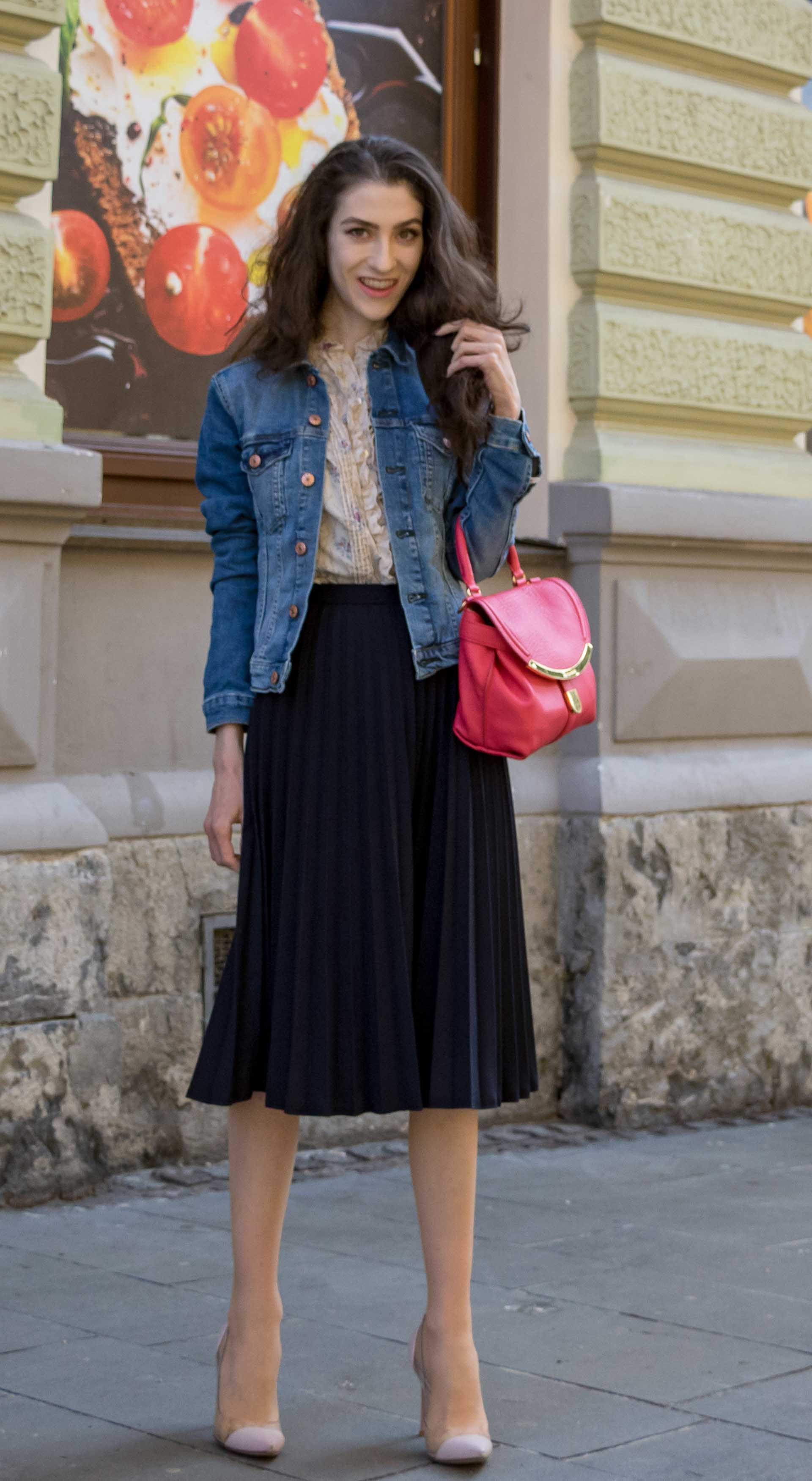 Veronika Lipar Fashion Blogger of Brunette from Wall Street dressed in H&M denim jacket, floral blouse, midi pleated skirt, Gianvito Rossi plexi pumps, pink top handle bag while standing on the street in Ljubljana