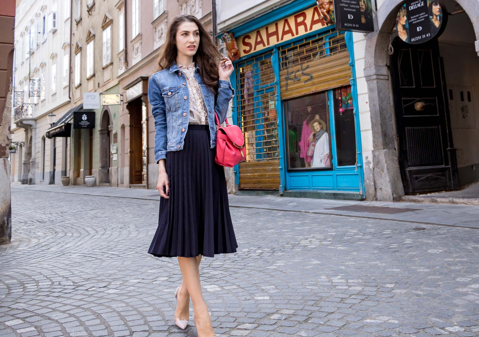 Veronika Lipar Fashion Blogger of Brunette from Wall Street dressed in H&M denim jacket, floral blouse, midi pleated skirt, Gianvito Rossi plexi pumps, pink top handle bag while walking on the street in Ljubljana