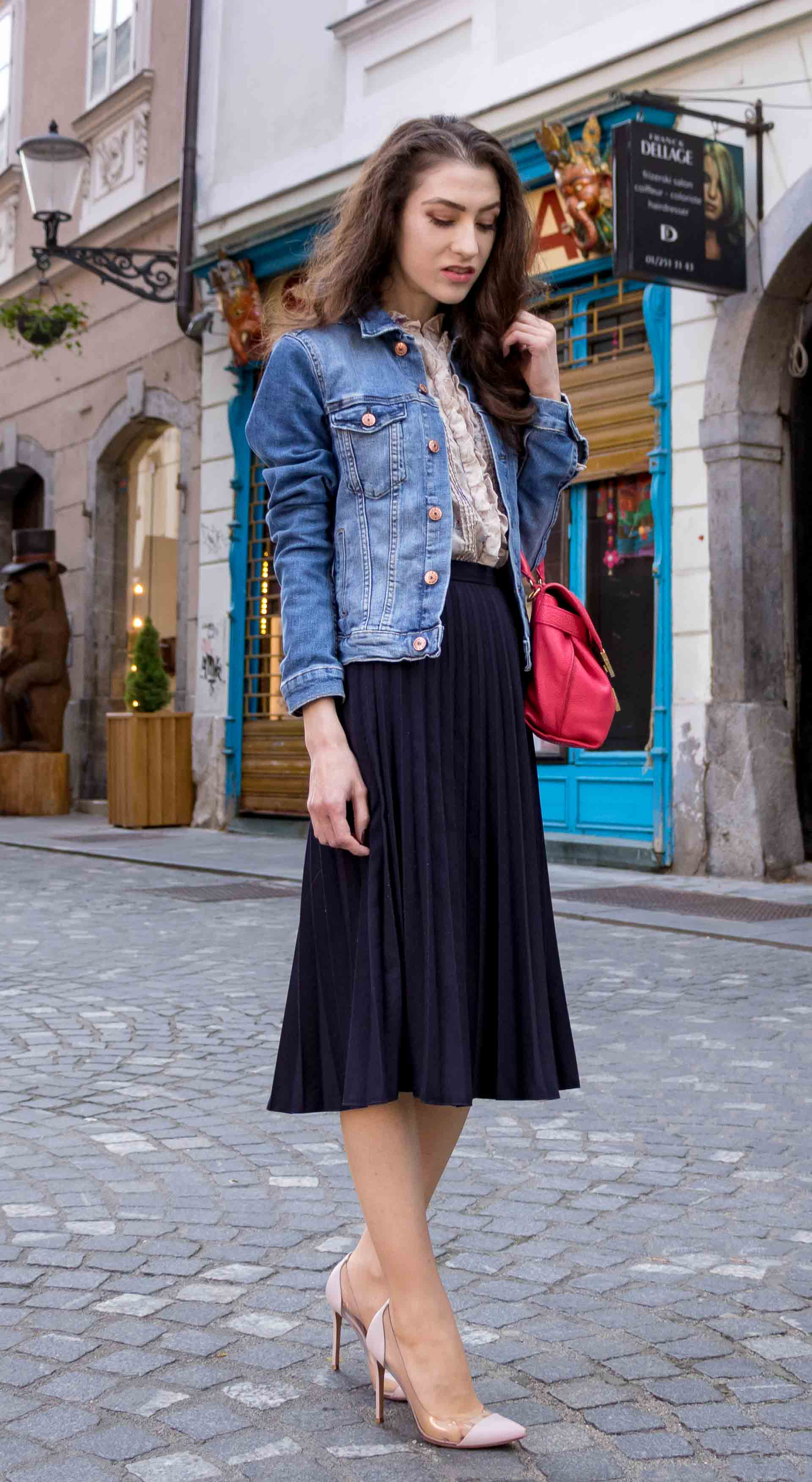 Veronika Lipar Fashion Blogger of Brunette from Wall Street wearing H&M denim jacket, floral blouse, midi pleated skirt, Gianvito Rossi plexi pumps, pink top handle bag while posing on the street in Ljubljana