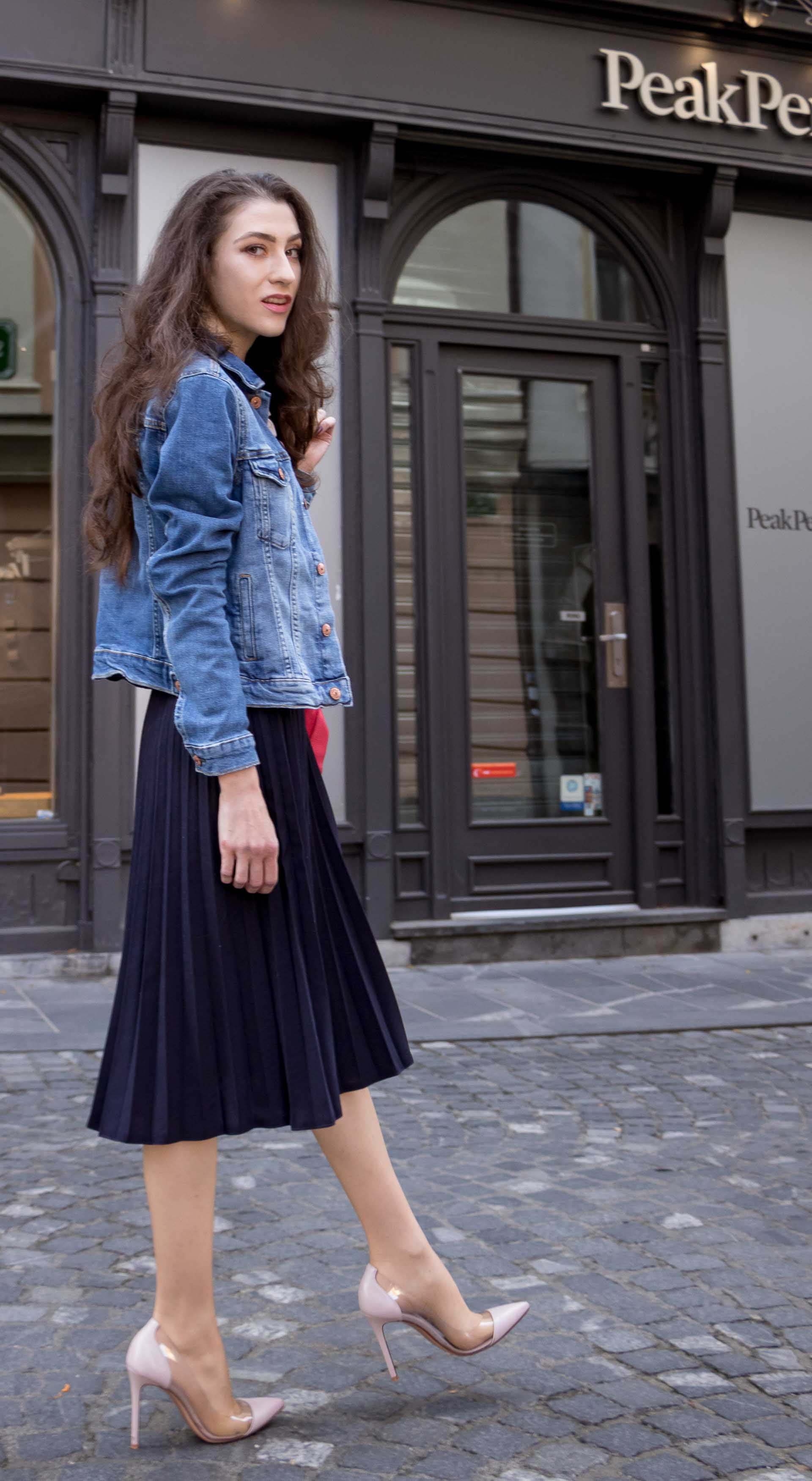 Veronika Lipar Fashion Blogger of Brunette from Wall Street dressed in H&M denim jacket, floral blouse, midi pleated skirt, Gianvito Rossi plexi pumps, pink top handle bag on cold summer morning