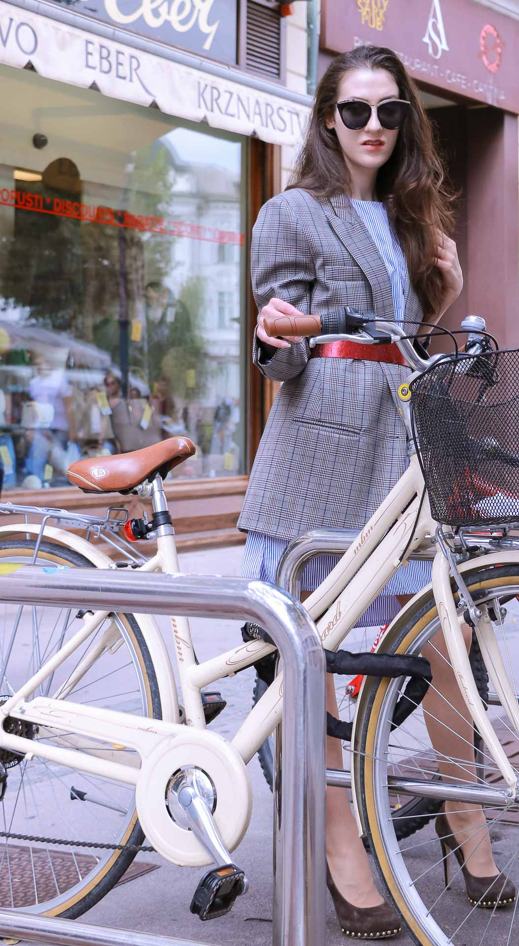 Veronika Lipar Fashion Blogger of Brunette from Wall Street dressed in Erika Cavallini plaid blazer, blue striped shirtdress, red belt, brown court shoes, black top handle bag, Le Specs black sunglasses while standing behind the bicycles