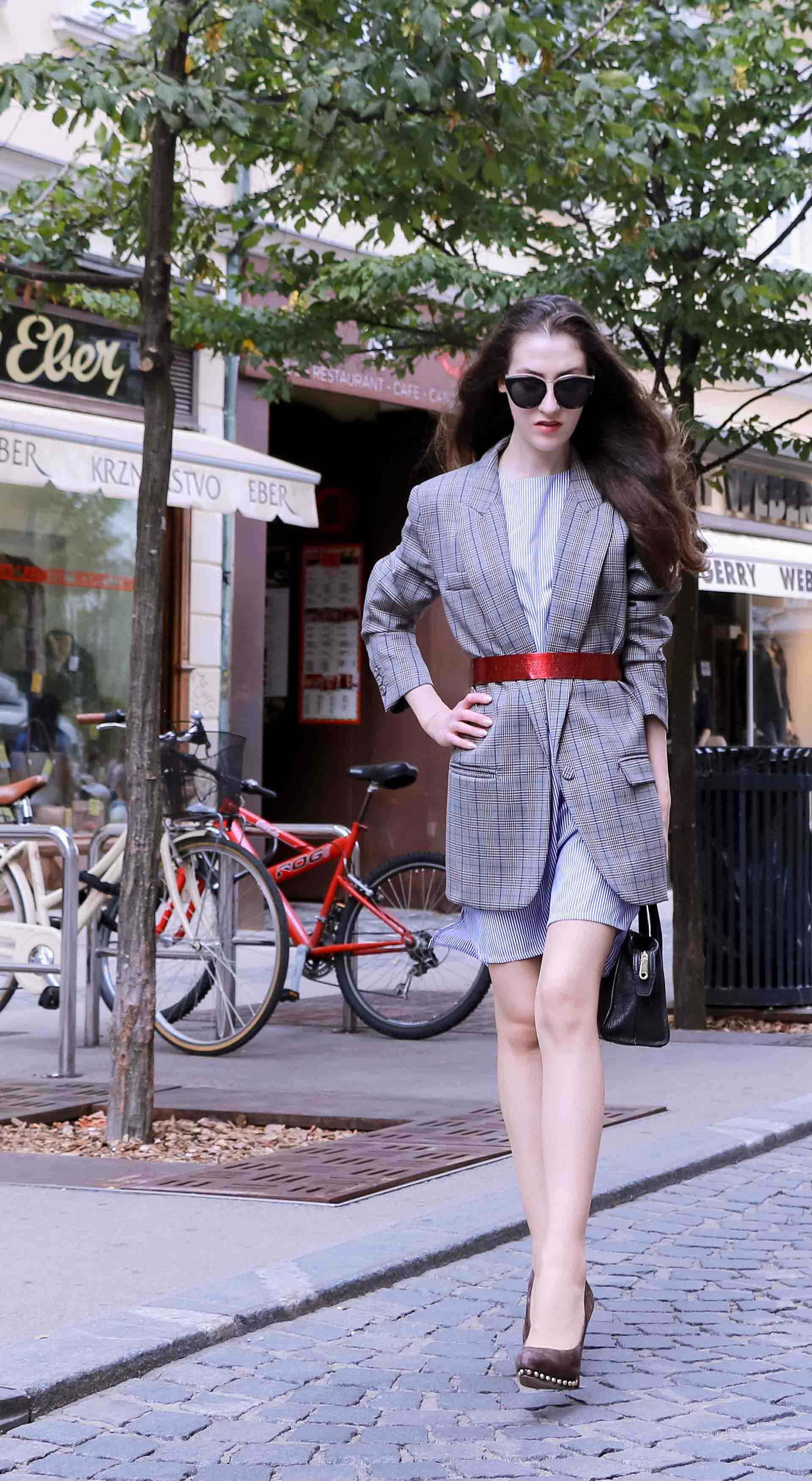 Veronika Lipar Fashion Blogger of Brunette from Wall Street dressed in Erika Cavallini plaid blazer, blue striped shirtdress, red belt, brown court shoes, black top handle bag, Le Specs black sunglasses in summer