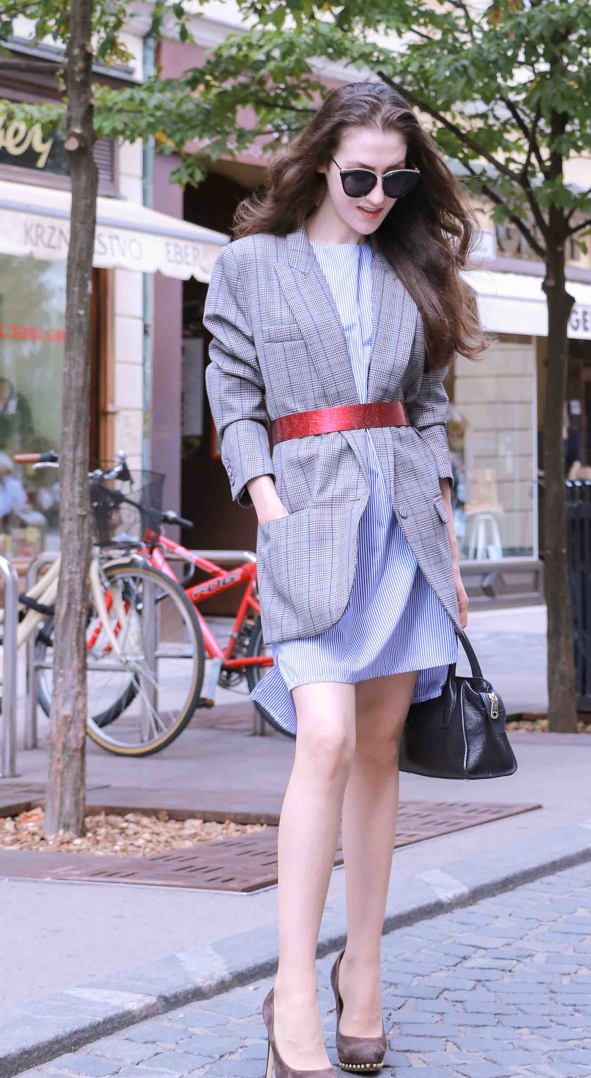 Veronika Lipar Fashion Blogger of Brunette from Wall Street wearing Erika Cavallini plaid blazer, blue striped shirtdress, red belt, brown court shoes, black top handle bag, Le Specs black shades while walking on the street