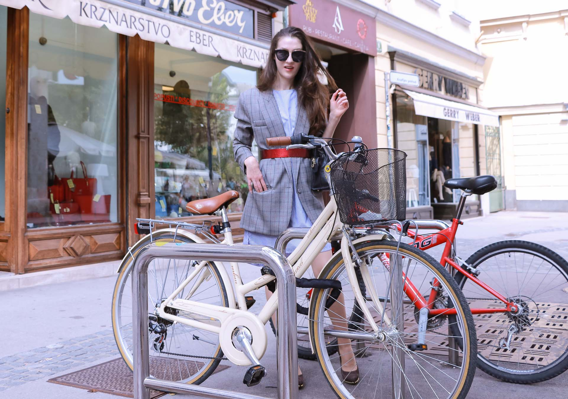 Veronika Lipar Fashion Blogger of Brunette from Wall Street wearing Erika Cavallini plaid blazer, blue striped shirtdress, red belt, brown court shoes, black top handle bag, Le Specs black sunglasses while standing behind the bicycles