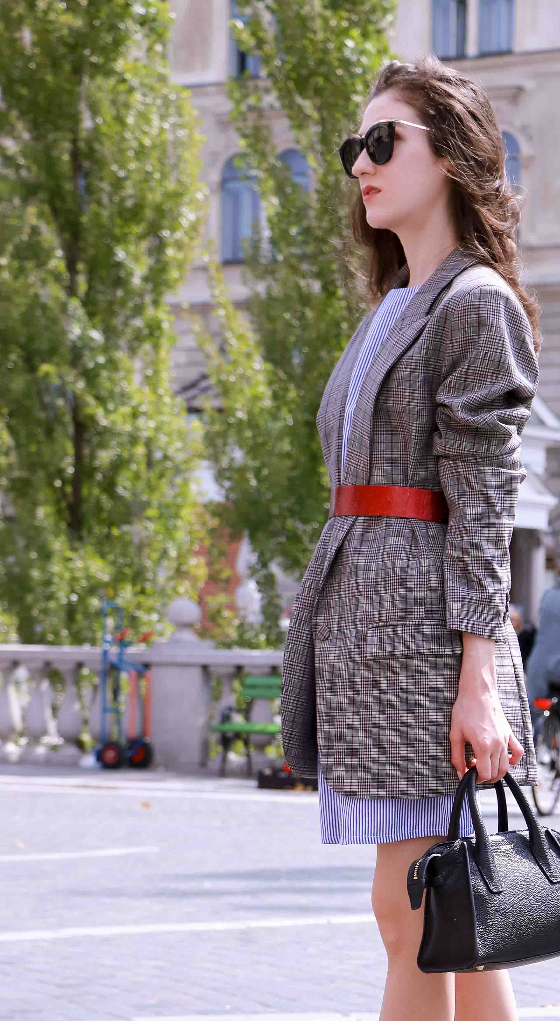 Veronika Lipar Fashion Blogger of Brunette from Wall Street dressed in Erika Cavallini plaid blazer, blue striped shirtdress, red belt, brown court shoes, black top handle bag, Le Specs black sunglasses while standing alone in Ljubljana