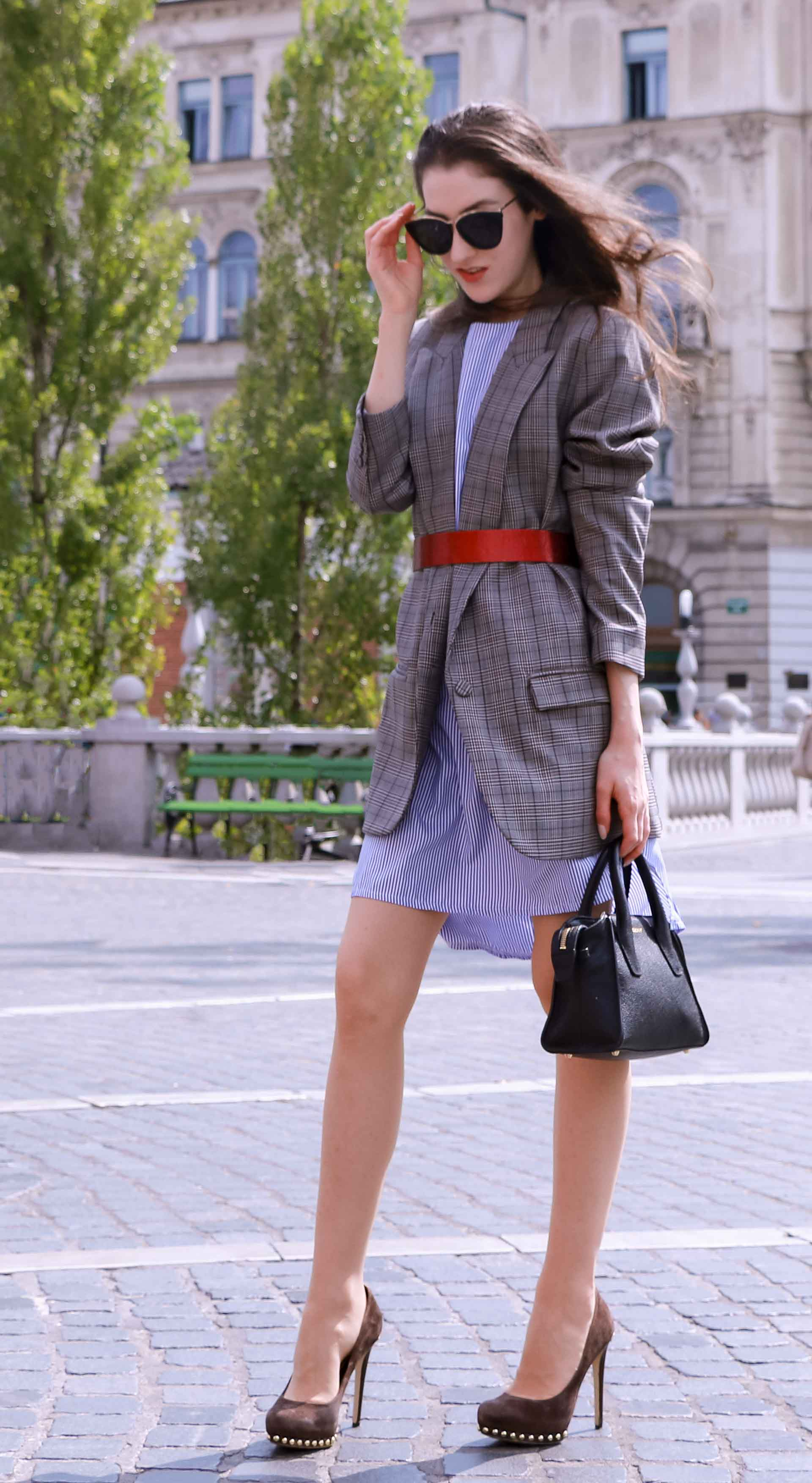 Veronika Lipar Fashion Blogger of Brunette from Wall Street wearing Erika Cavallini plaid blazer, blue striped shirtdress, red belt, brown court shoes, black top handle bag, Le Specs black shades while standing at the Prešeren square