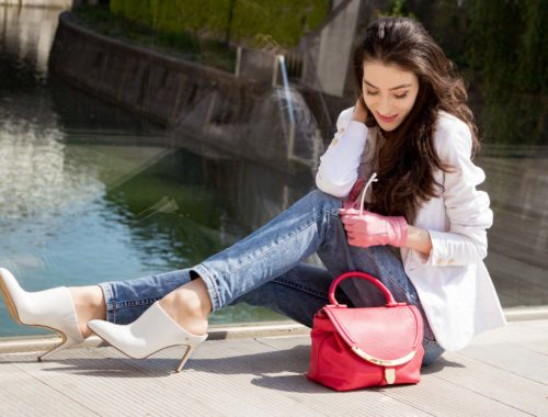 Veronika Lipar Fashion Blogger of Brunette from Wall Street wearing white mules, blue A.P.C. mom jeans, white fringe blouse, white blazer, pink gloves, pink top handle bag and Le Specs Lolita white cat eye sunglasses while sitting on the bridge