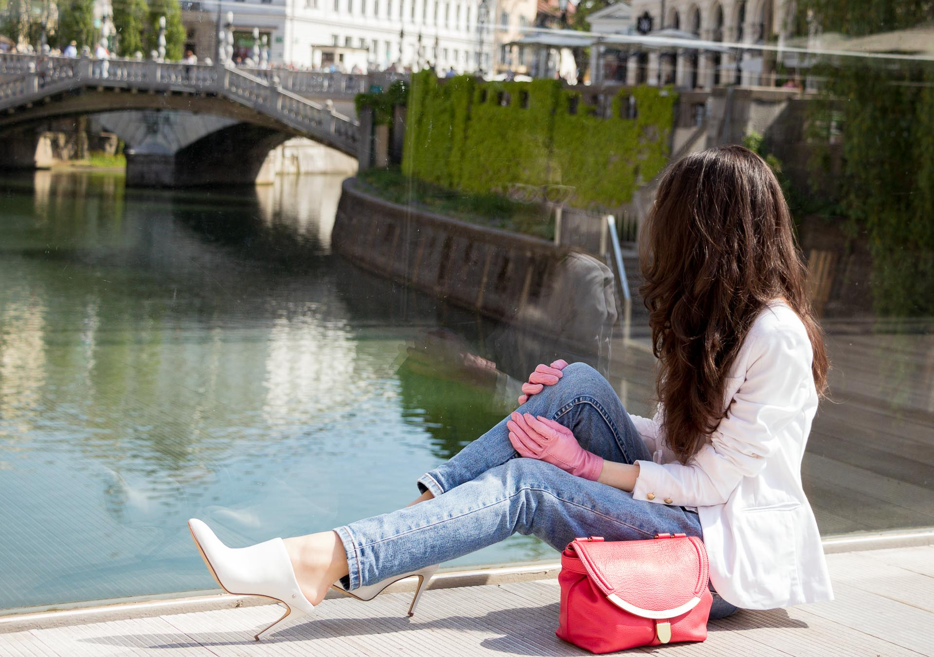 Veronika Lipar Fashion Blogger of Brunette from Wall Street dressed in white mules, blue A.P.C. mom jeans, white fringe blouse, white blazer, pink gloves, pink top handle bag and Le Specs Lolita white cat eye sunglasses while sitting on the floor on the bridge in Ljubljana