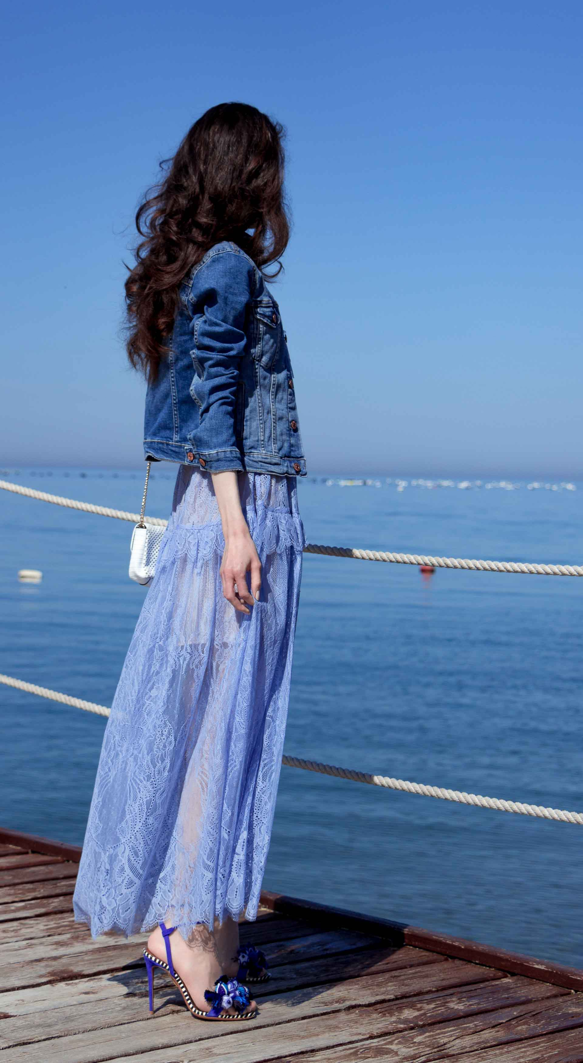 Veronika Lipar Fashion Blogger of Brunette from Wall Street wearing blue off the shoulder midi lace dress from Self-Portrait, H&M blue denim jacket, white chain shoulder bag, Aquazzura blue pom pom tassels sandals, white Lolita cat-eye sunglasses for romantic summer date at the seaside
