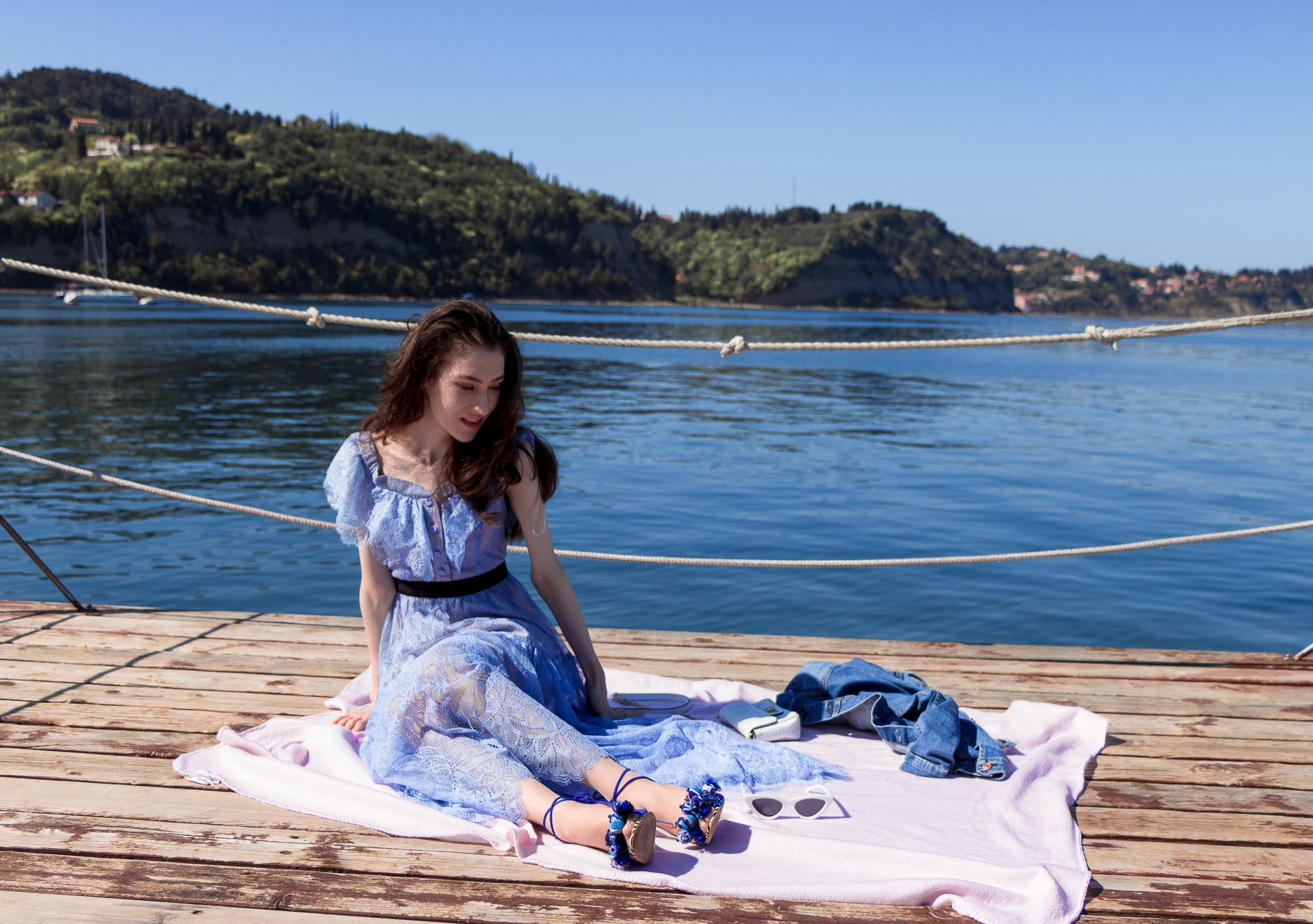 Veronika Lipar Fashion Blogger of Brunette from Wall Street wearing blue off the shoulder midi lace dress from Self-Portrait, white chain shoulder bag, Aquazzura blue pom pom tassels sandals, white Lolita cat-eye sunglasses while sitting on a picnic blanket by the sea