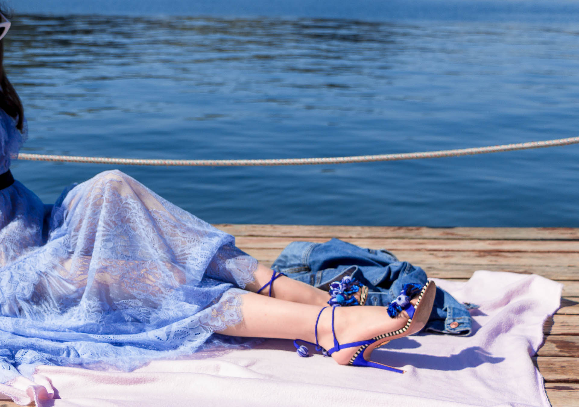 Veronika Lipar Fashion Blogger of Brunette from Wall Street dressed in blue off the shoulder midi lace dress from Self-Portrait, white chain shoulder bag, Aquazzura blue pom pom tassels sandals, white Lolita cat-eye sunglasses while sitting on a picnic blanket by the sea