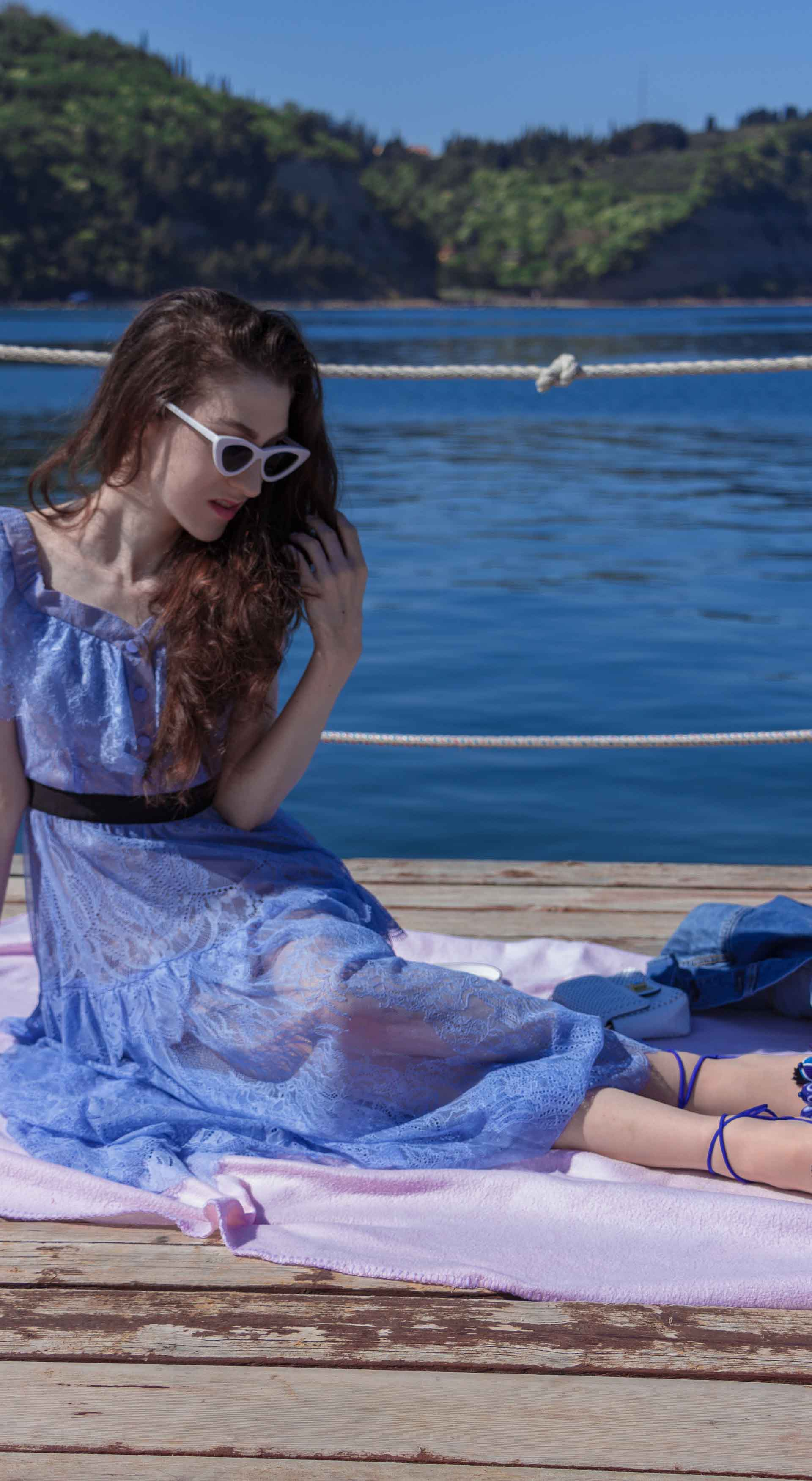 Veronika Lipar Fashion Blogger of Brunette from Wall Street wearing blue off the shoulder midi lace dress from Self-Portrait, white chain shoulder bag, Aquazzura blue pom pom tassels sandals, white Lolita cat-eye sunglasses while sitting on a picnic blanket by the lake