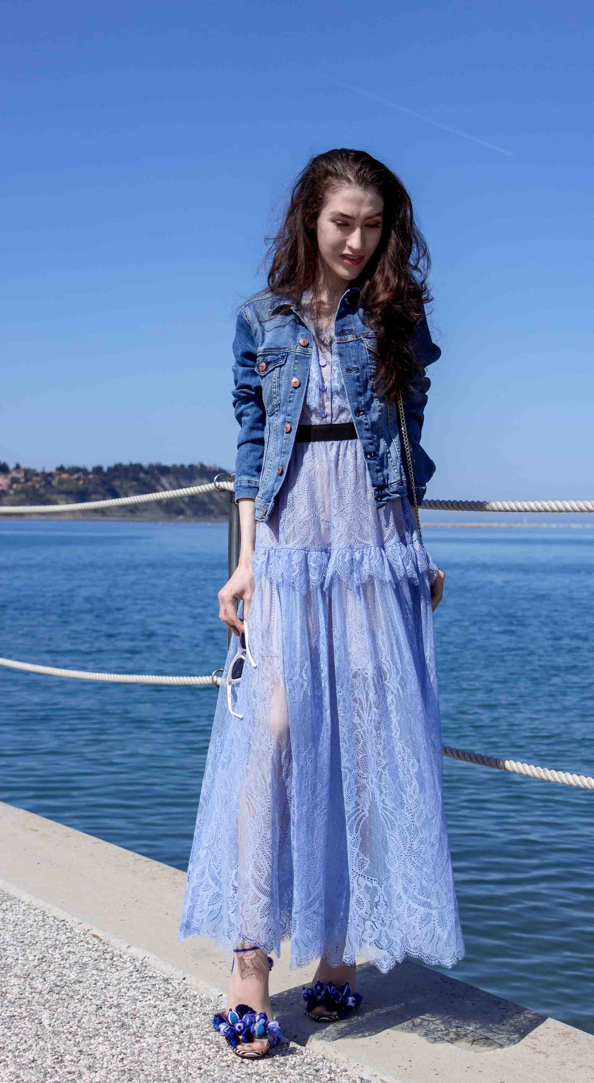 Veronika Lipar Fashion Blogger of Brunette from Wall Street wearing blue off the shoulder midi lace dress from Self-Portrait, H&M blue denim jacket, white chain shoulder bag, Aquazzura blue pom pom tassels sandals, white Lolita cat-eye sunglasses for romantic summer date by the sea