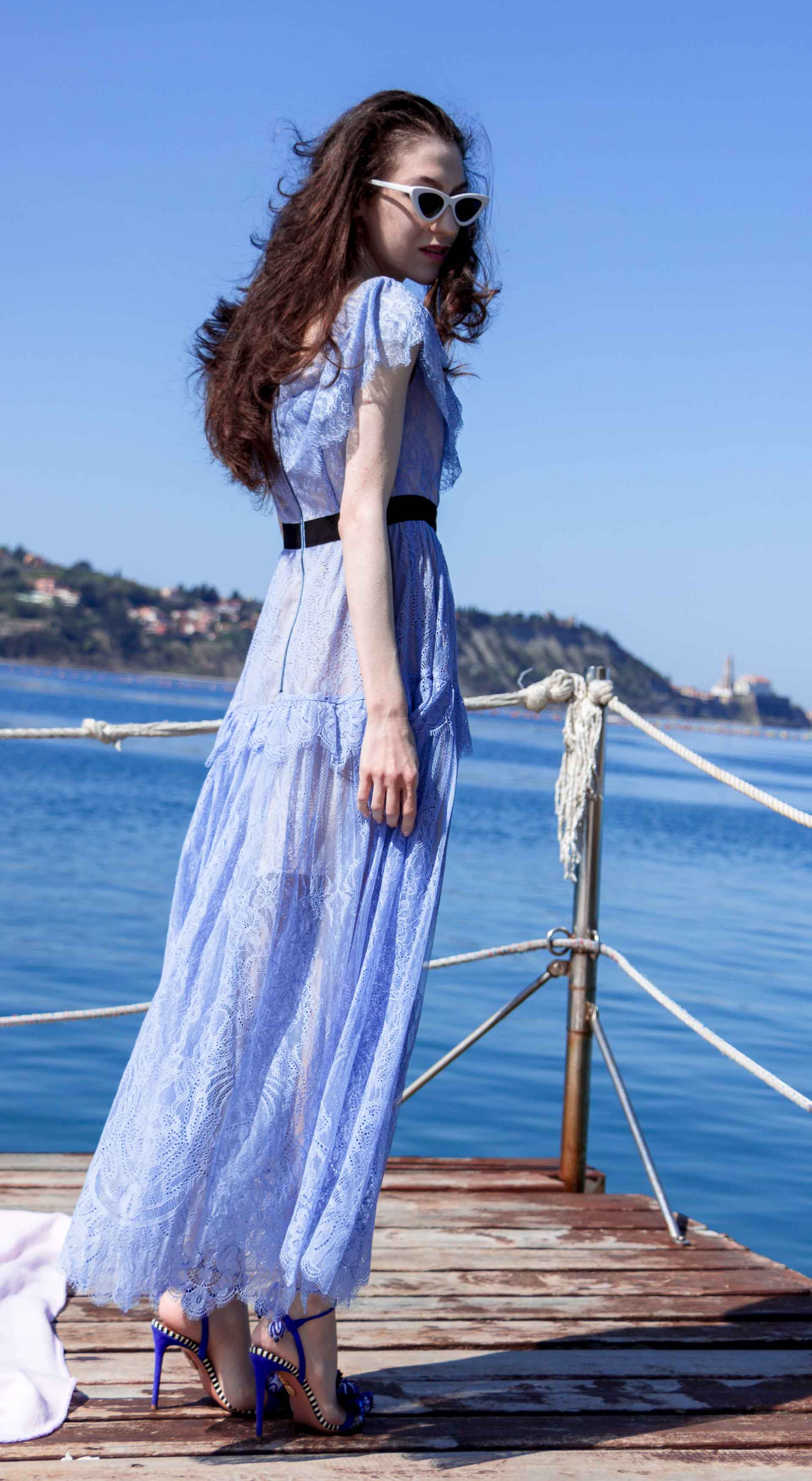 Veronika Lipar Fashion Blogger of Brunette from Wall Street wearing blue off the shoulder midi lace dress from Self-Portrait, white chain shoulder bag, Aquazzura blue pom pom tassels sandals, white Lolita cat-eye sunglasses for romantic summer date at the seaside