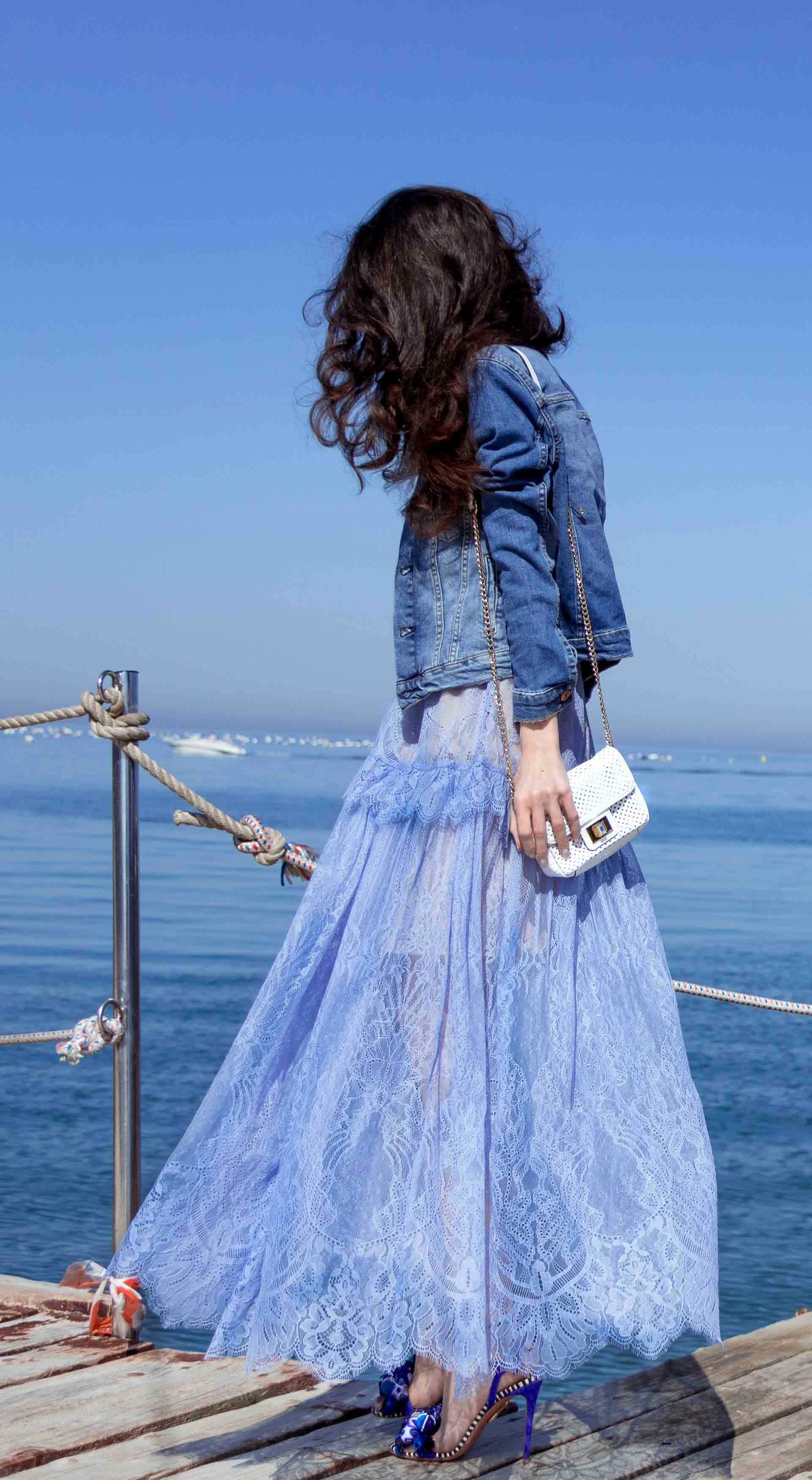 Veronika Lipar Fashion Blogger of Brunette from Wall Street dressed in blue off the shoulder midi lace dress from Self-Portrait, H&M blue denim jacket, white chain shoulder bag, Aquazzura blue pom pom tassels sandals, white Lolita cat-eye sunglasses on a date at the seaside