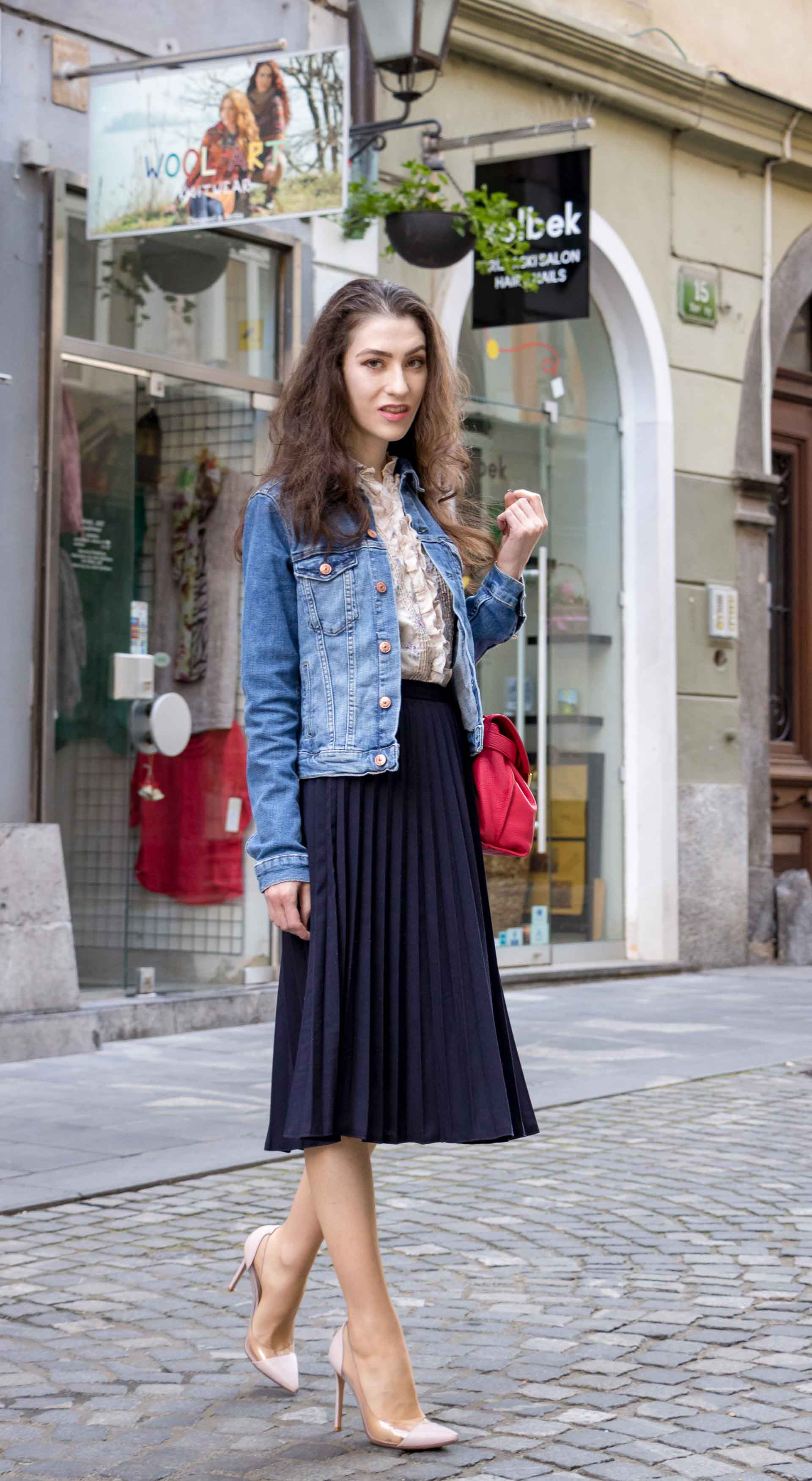 Veronika Lipar Fashion Blogger of Brunette from Wall Street dressed in H&M denim jacket, floral blouse, midi pleated skirt, Gianvito Rossi plexi pumps, pink top handle bag looking cool and elegant