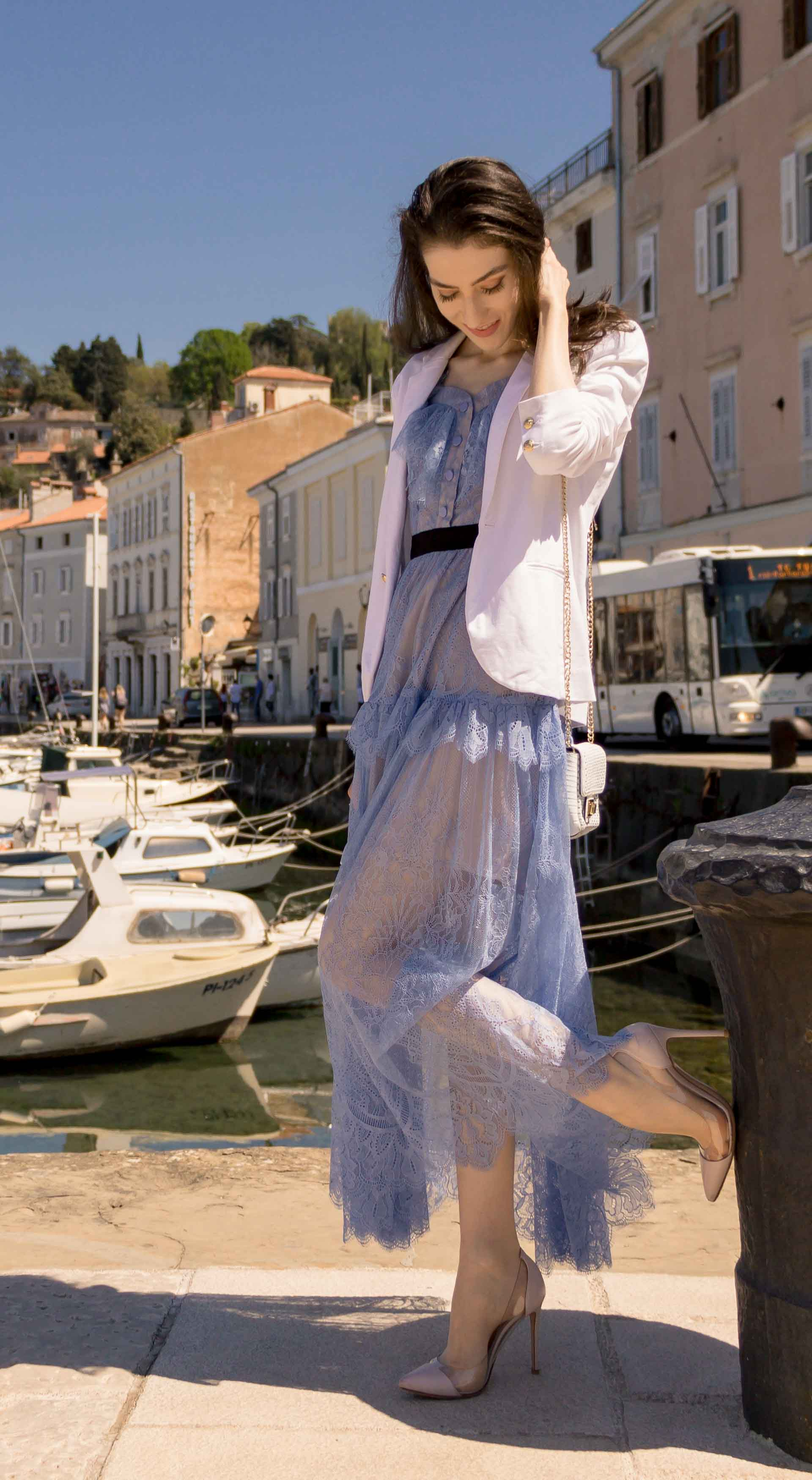 Veronika Lipar Fashion Blogger of Brunette from Wall Street wearing Self-Portrait blue lace dress, white single button blazer, blush Gianvito Rossi plexi pumps, white shoulder bag, Lespecs white cat eye sunglasses while standing in the port in Piran