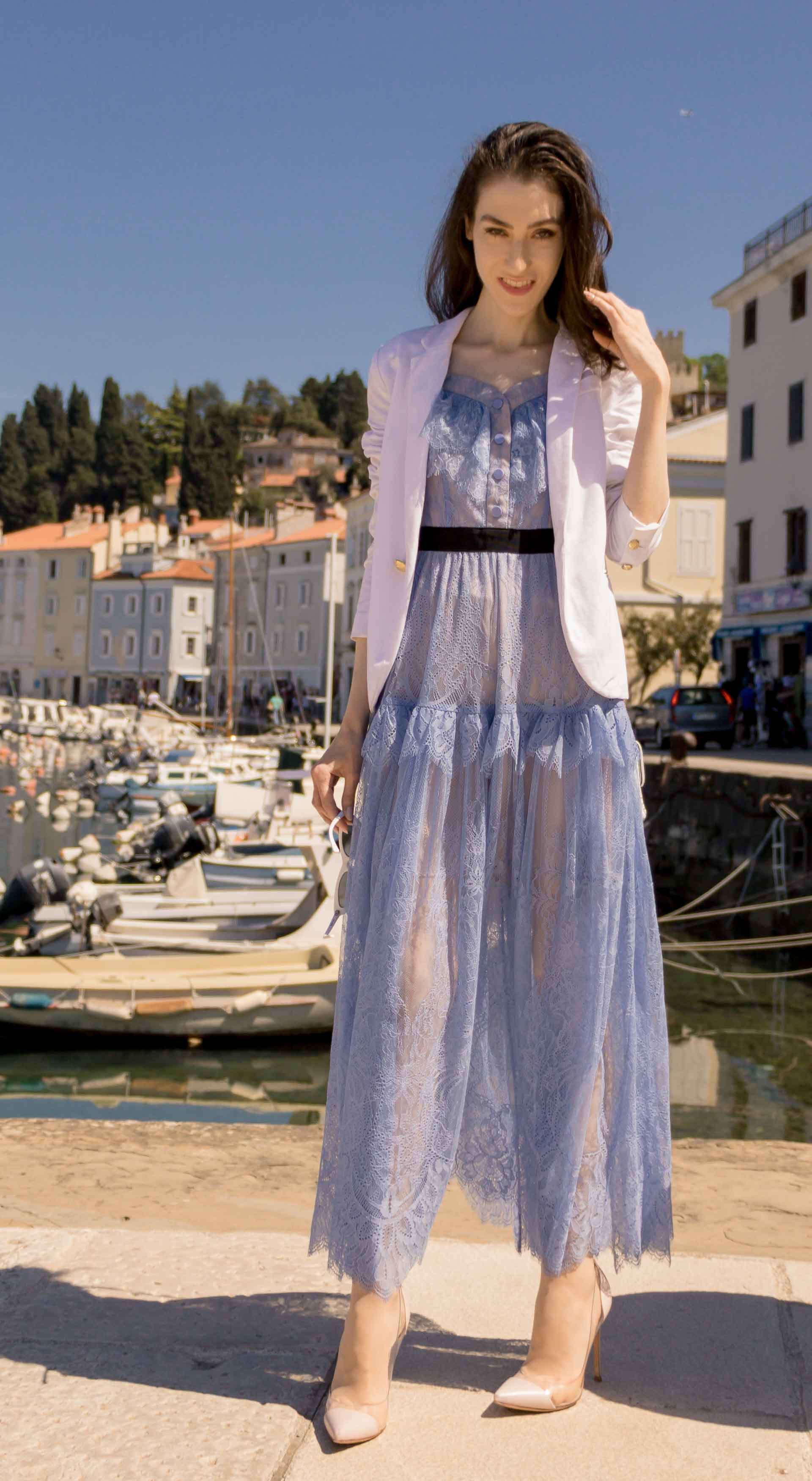 Veronika Lipar Fashion Blogger of Brunette from Wall Street dressed in Self-Portrait blue lace dress, white single button blazer, blush Gianvito Rossi plexi pumps, white shoulder bag, Lespecs white cat eye sunglasses while standing in the port in Piran