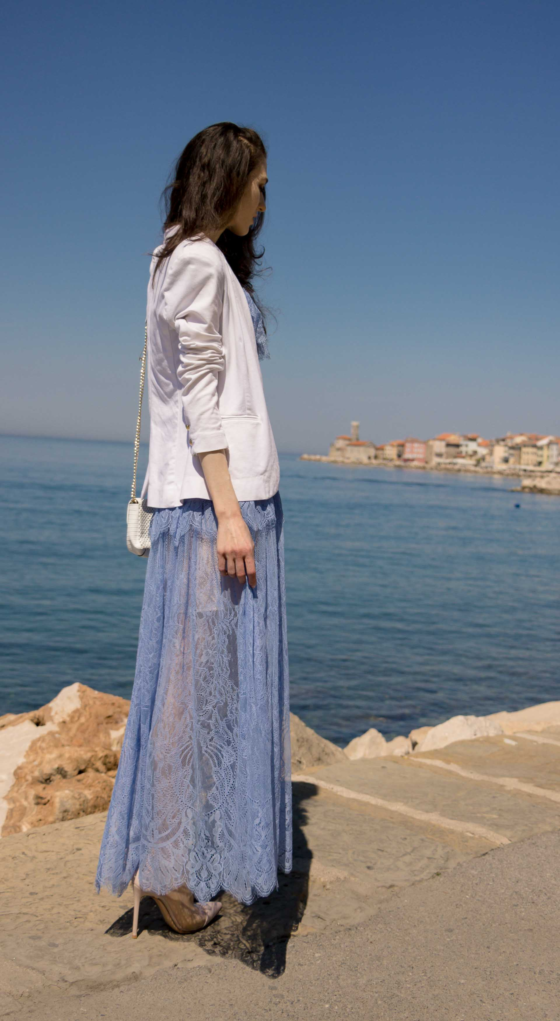 Veronika Lipar Fashion Blogger of Brunette from Wall Street wearing Self-Portrait blue lace midi dress, white single button blazer, blush Gianvito Rossi plexi pumps, white shoulder bag, Lespecs white cat eye sunglasses while looking at the ocean