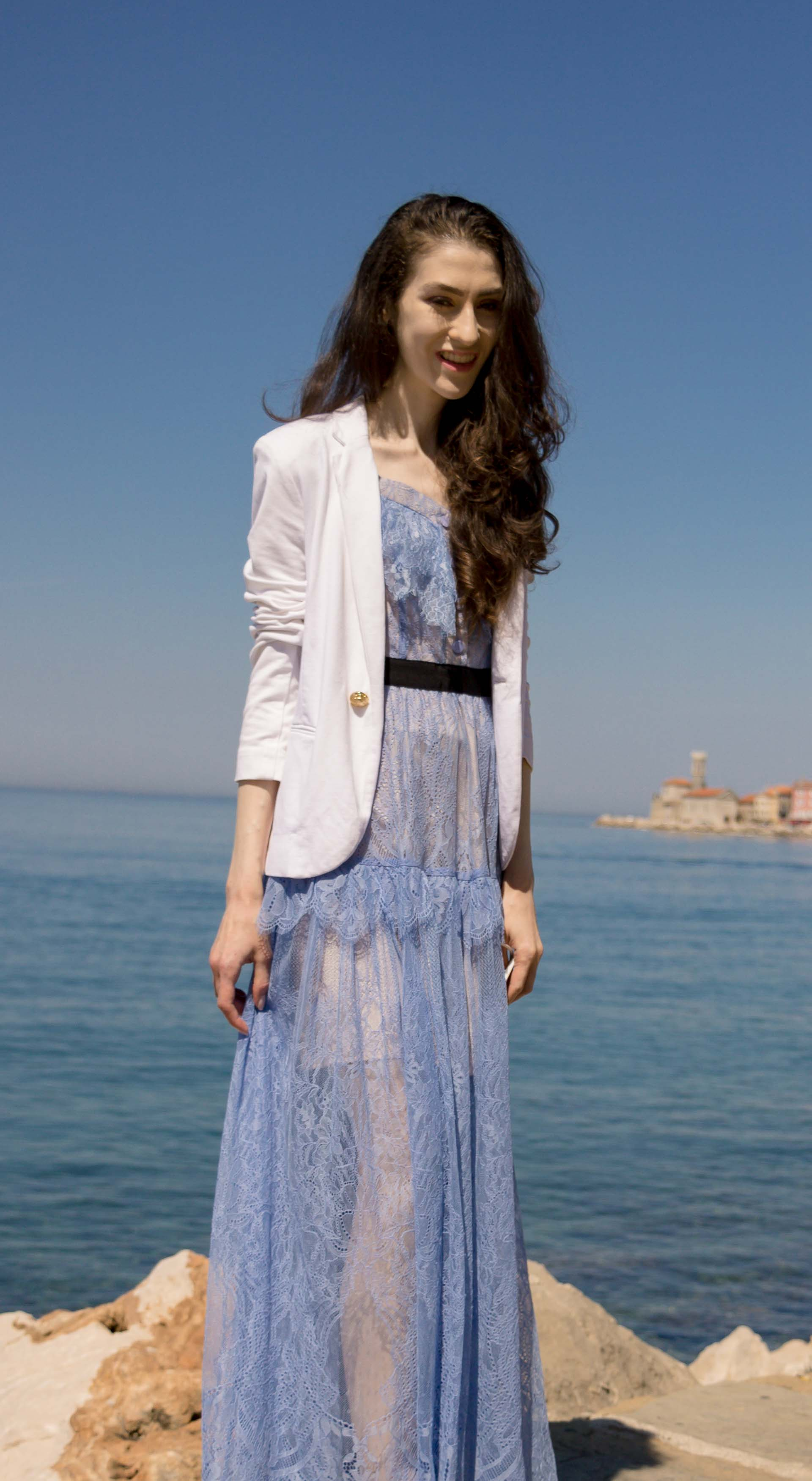 Veronika Lipar Fashion Blogger of Brunette from Wall Street wearing Self-Portrait blue lace midi dress, white single button blazer, white shoulder bag, for a wedding by the sea