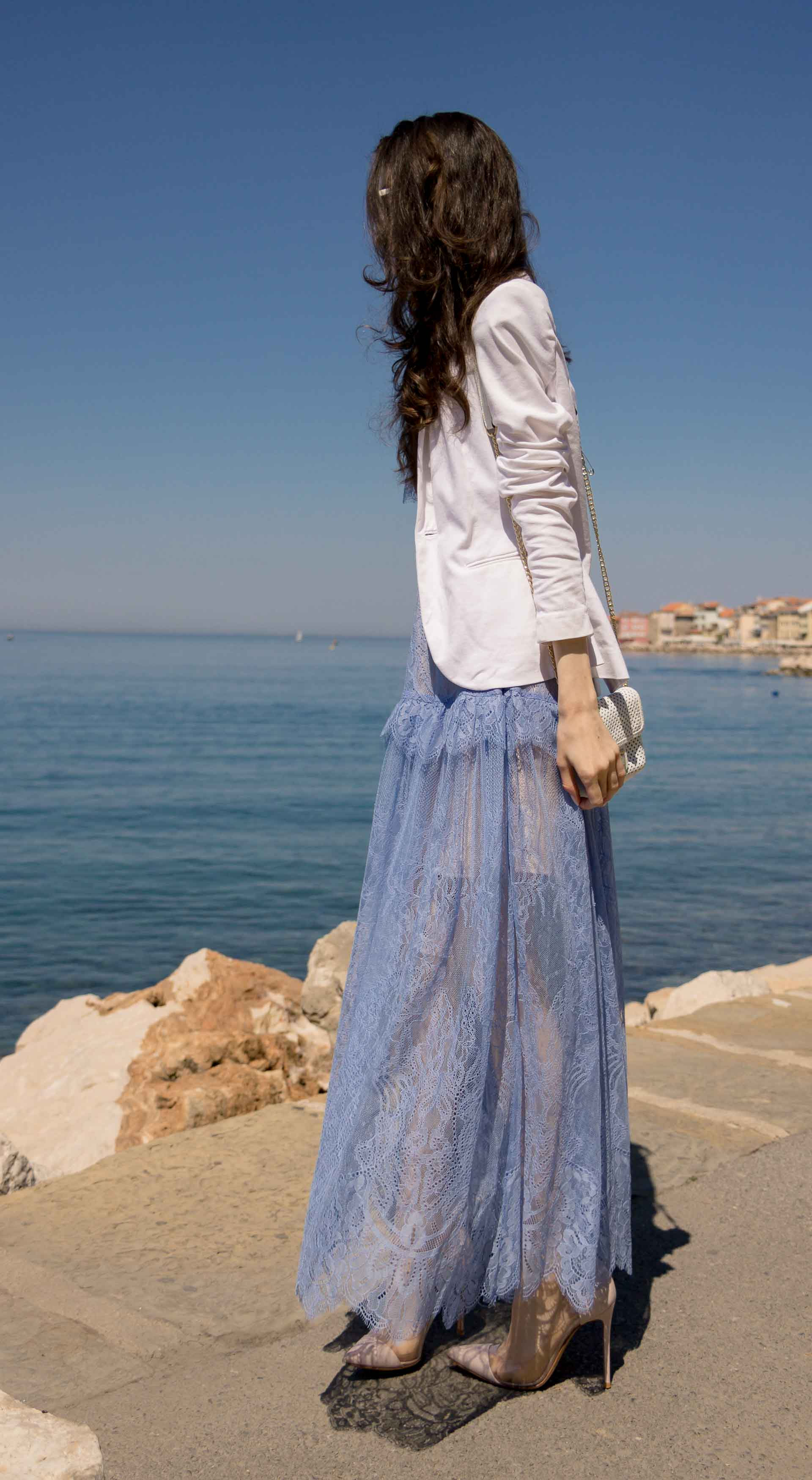 Veronika Lipar Fashion Blogger of Brunette from Wall Street wearing Self-Portrait blue lace midi dress, white single button blazer, blush Gianvito Rossi plexi pumps, white shoulder bag, Lespecs white cat eye sunglasses while standing by the sea
