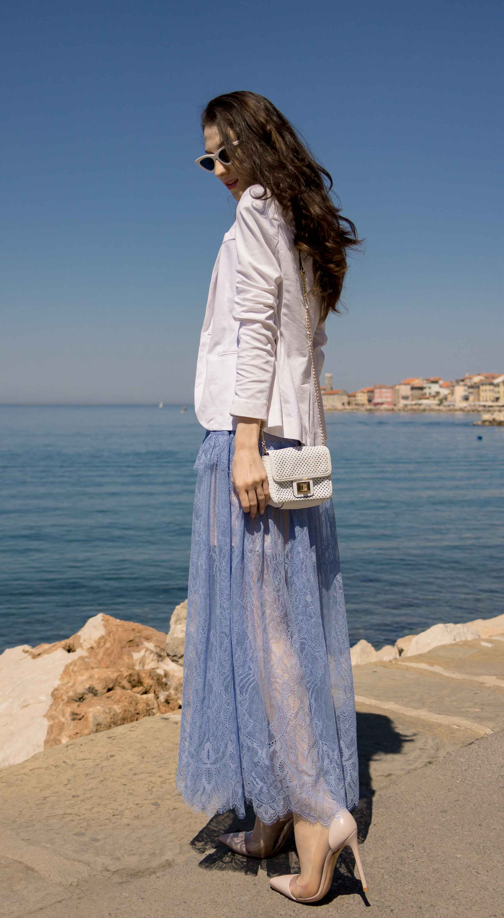 Veronika Lipar Fashion Blogger of Brunette from Wall Street wearing Self-Portrait blue lace midi dress, white single button blazer, blush Gianvito Rossi plexi pumps, white shoulder bag, Lespecs white cat eye sunglasses for a wedding by the sea