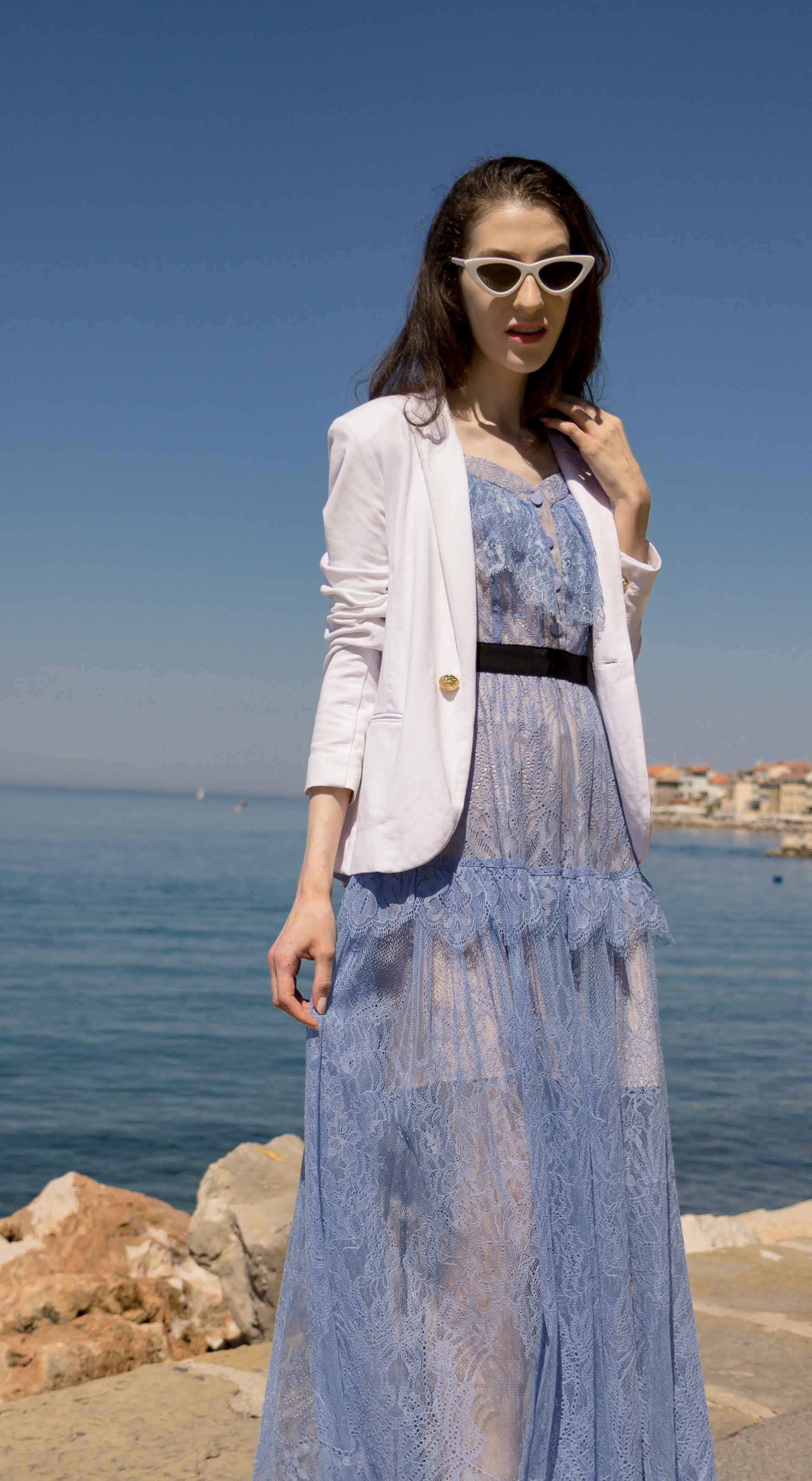 Veronika Lipar Fashion Blogger of Brunette from Wall Street wearing Self-Portrait blue lace midi dress, white single button blazer, white shoulder bag, Lespecs white cat eye sunglasses for a wedding by the sea