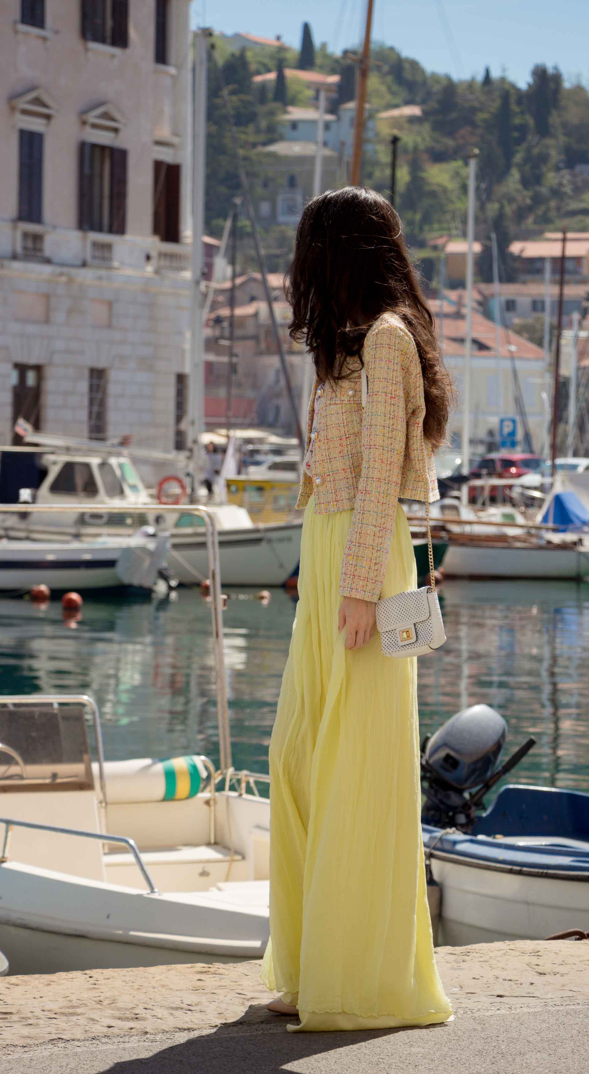 Veronika Lipar Fashion Blogger of Brunette from Wall Street wearing long yellow tulle skirt from Needle & Thread, short yellow tweed jacket from Storets, floral sik top, blush Gianvito Rossi plexi pumps, white shoulder bag, Lespecs white cat eye sunglasses walking at the port in Venice
