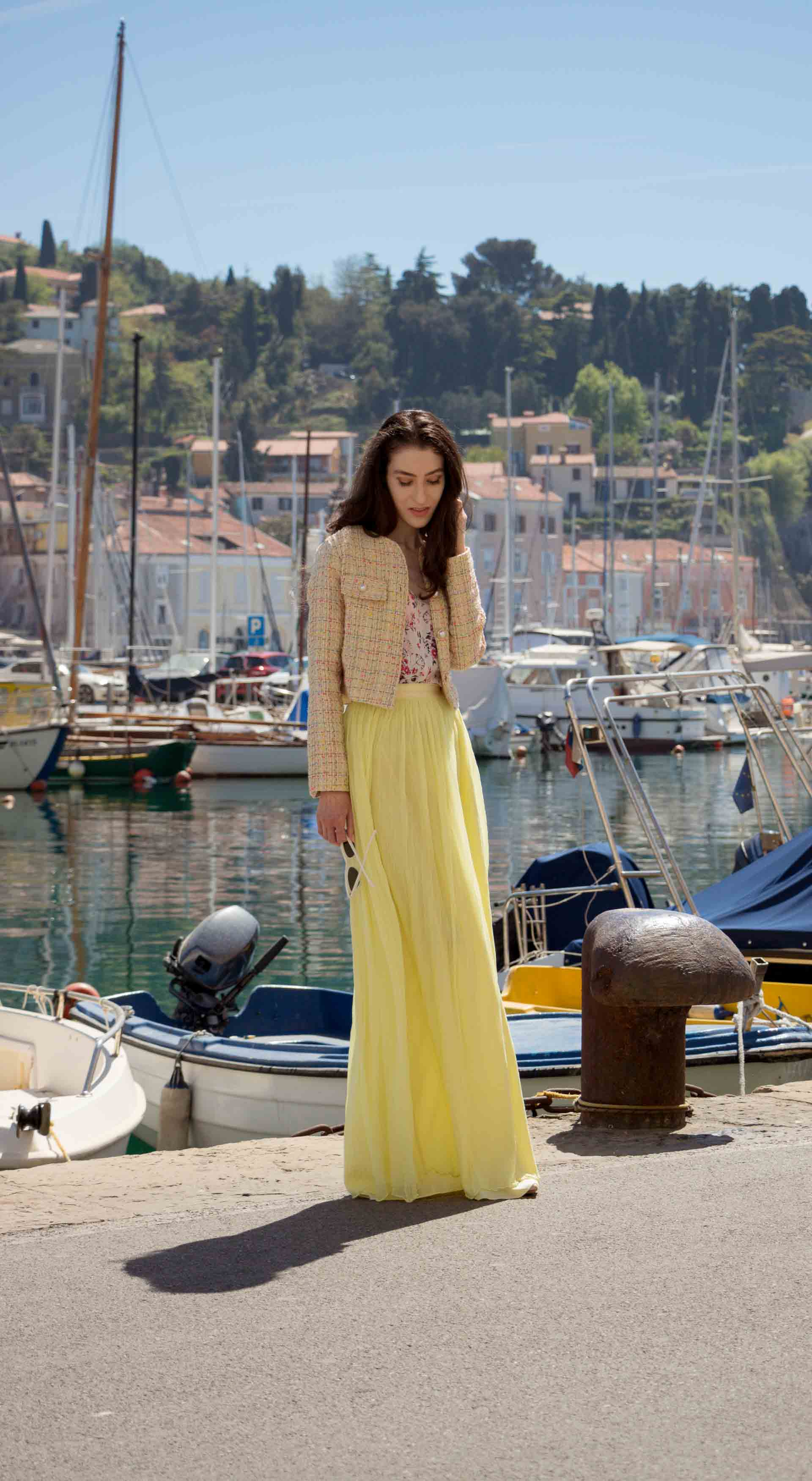 Veronika Lipar Fashion Blogger of Brunette from Wall Street wearing maxi yellow tulle skirt from Needle & Thread, short yellow tweed jacket from Storets, floral silk top, blush Gianvito Rossi plexi pumps, white shoulder bag, Lespecs white cat eye sunglasses while walking at the port in Venice