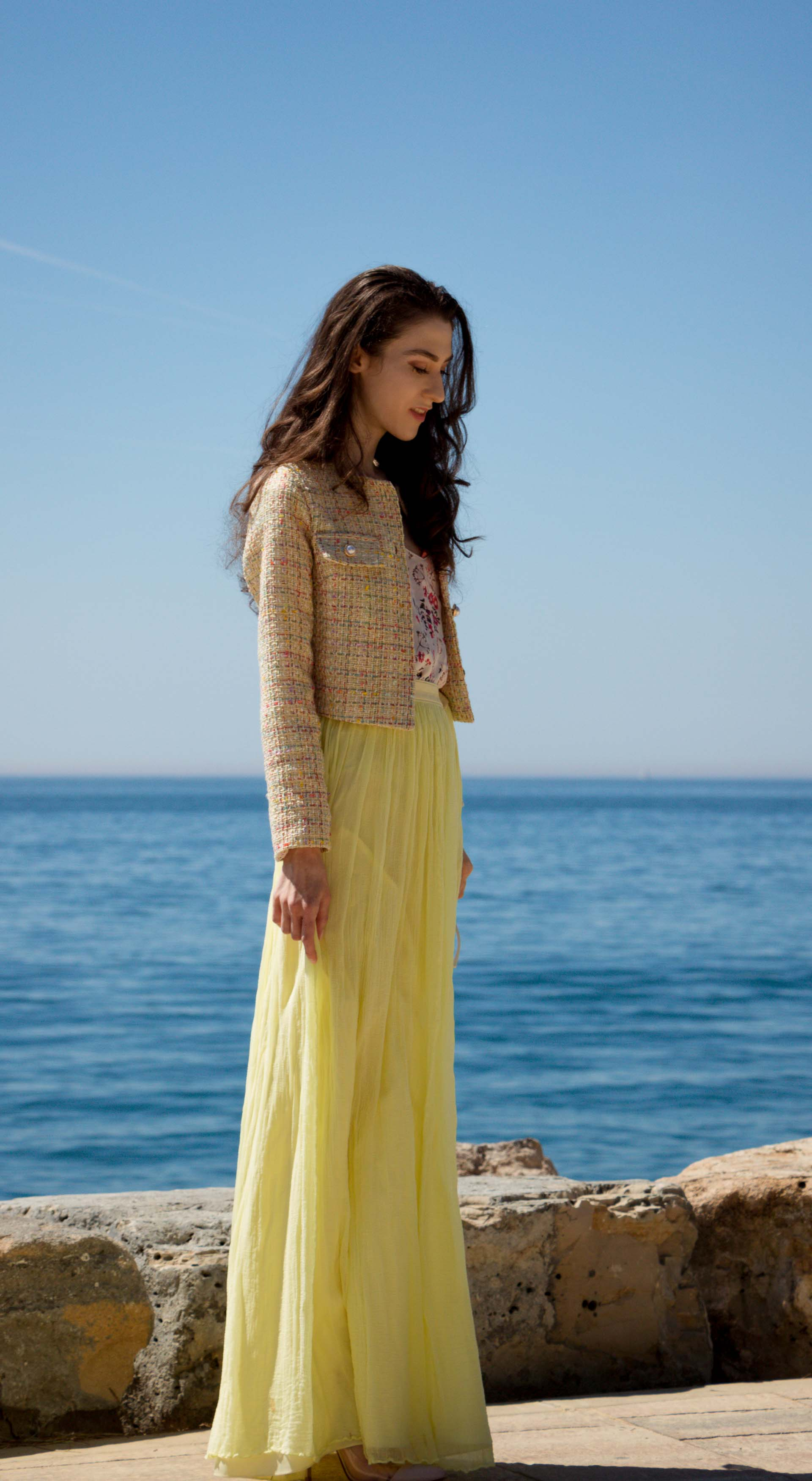 Veronika Lipar Fashion Blogger of Brunette from Wall Street wearing maxi yellow tulle skirt from Needle & Thread, short yellow tweed jacket from Storets, floral silk top, blush Gianvito Rossi plexi pumps, white shoulder bag by the sea