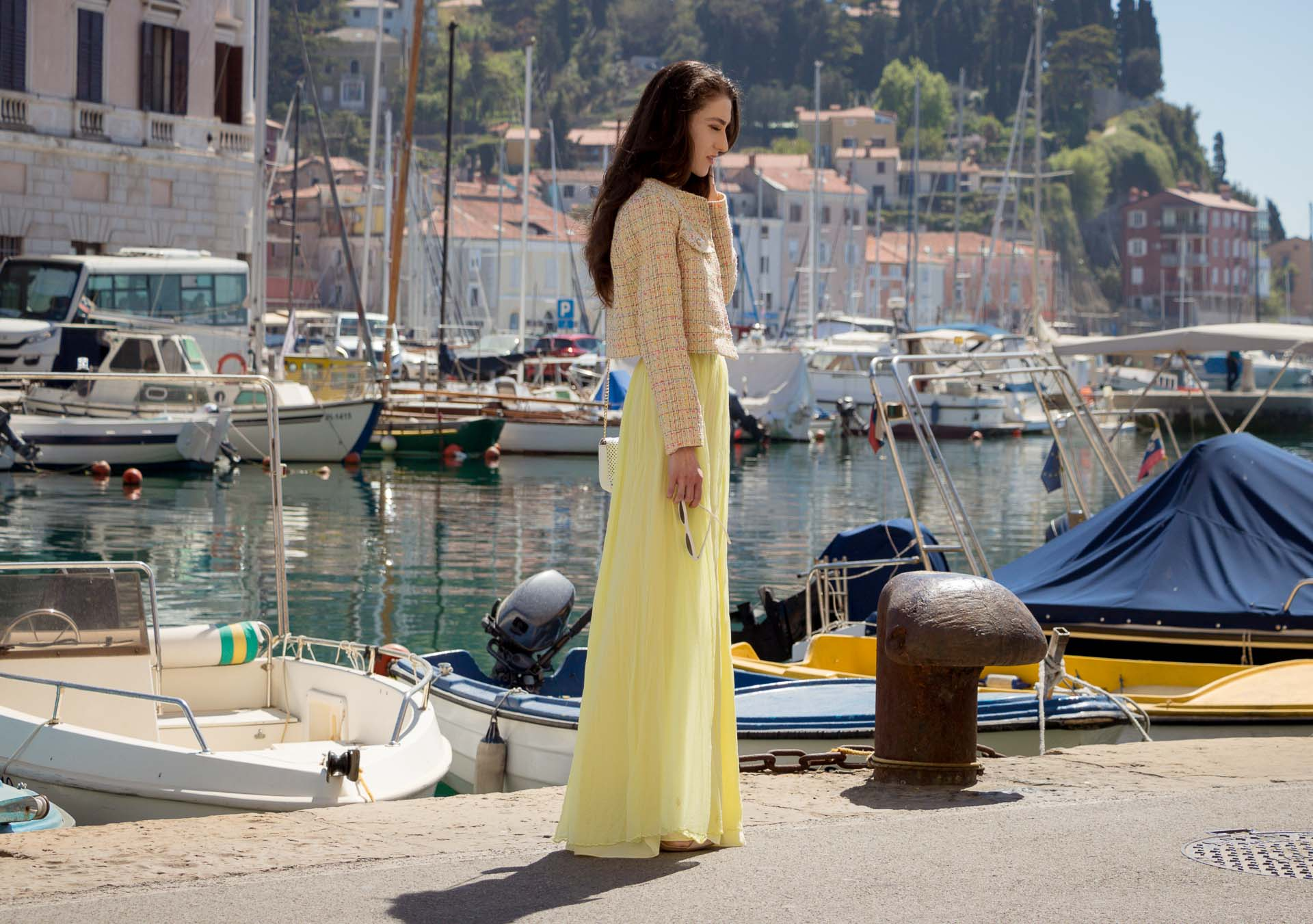Veronika Lipar Fashion Blogger of Brunette from Wall Street wearing long yellow tulle skirt from Needle & Thread, short yellow tweed jacket from Storets, floral silk top, blush Gianvito Rossi plexi pumps, white shoulder bag, Le specs white cat eye sunglasses walking at the port in Venice