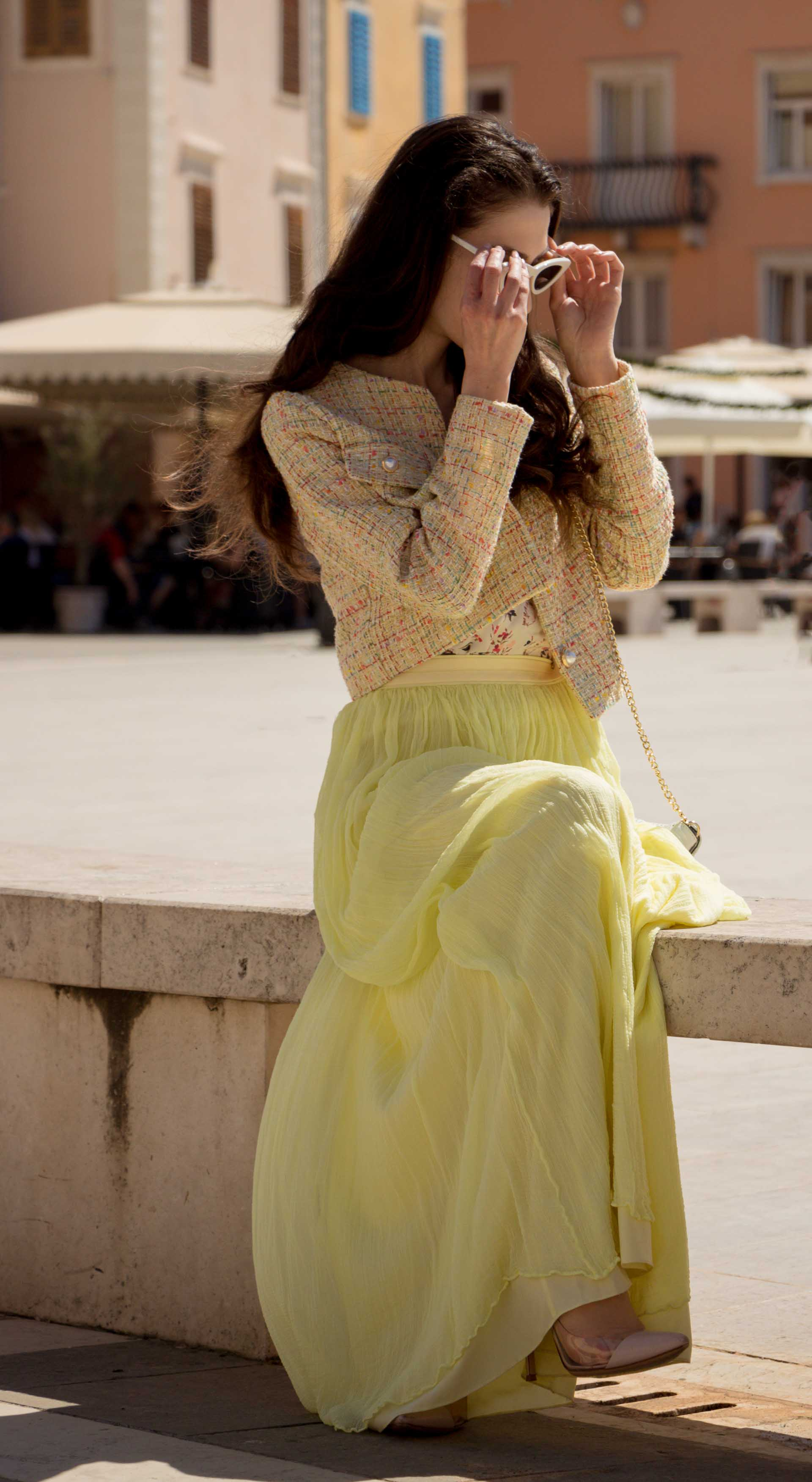 Veronika Lipar Fashion Blogger of Brunette from Wall Street wearing long yellow tulle skirt from Needle & Thread, short yellow tweed jacket from Storets, floral sik top, blush Gianvito Rossi plexi pumps, white shoulder bag, Lespecs white cat eye sunglasses while sitting at the square in Piran