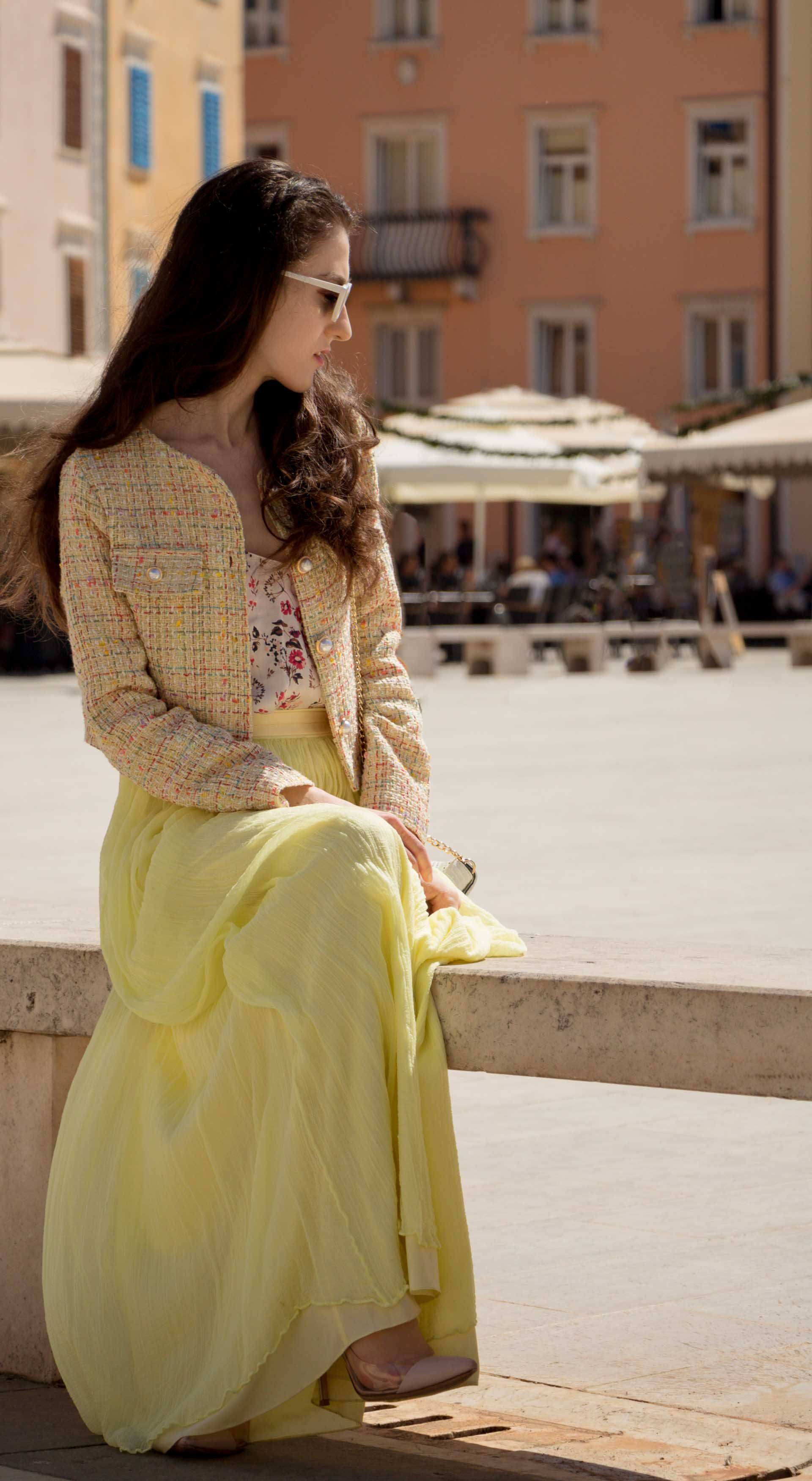 Veronika Lipar Fashion Blogger of Brunette from Wall Street wearing maxi yellow tulle skirt from Needle & Thread, short yellow tweed jacket from Storets, floral sik top, blush Gianvito Rossi plexi pumps, white shoulder bag, Lespecs white cat eye sunglasses while sitting at the square in Piran