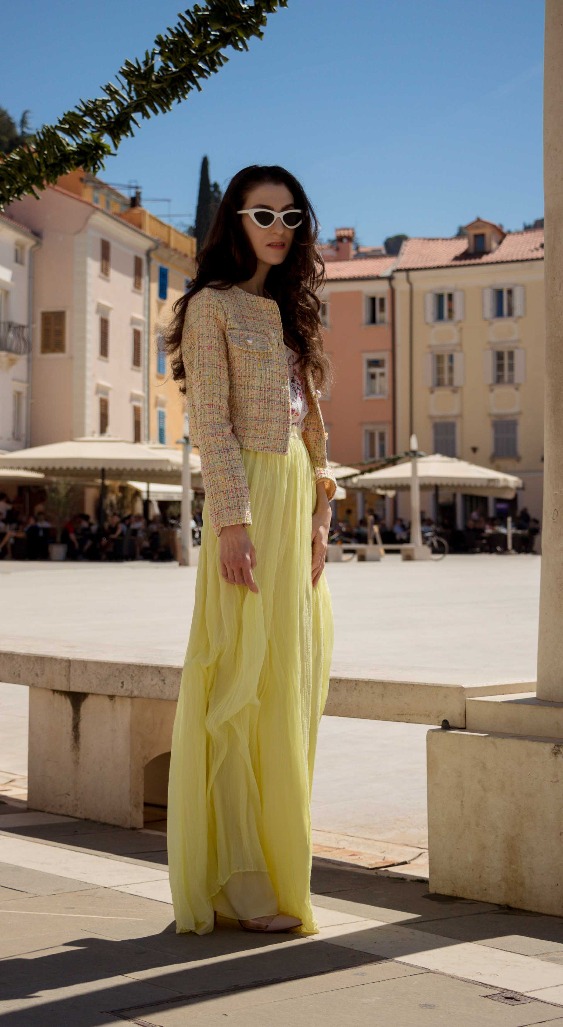 Veronika Lipar Fashion Blogger of Brunette from Wall Street wearing maxi yellow tulle skirt from Needle & Thread, short yellow tweed jacket from Storets, floral sik top, blush Gianvito Rossi plexi pumps, white shoulder bag while standing at the square in Piran