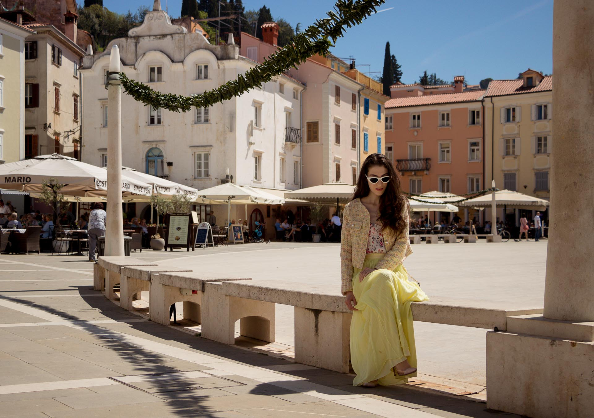 Veronika Lipar Fashion Blogger of Brunette from Wall Street wearing maxi yellow tulle skirt from Needle & Thread, short yellow tweed jacket from Storets, floral silk top, blush Gianvito Rossi plexi pumps, white shoulder bag, Le specs white cat eye sunglasses while sitting at the square in Pirano