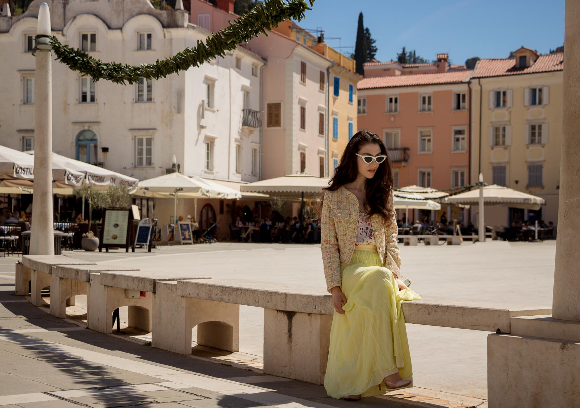 Veronika Lipar Fashion Blogger of Brunette from Wall Street wearing maxi yellow tulle skirt from Needle & Thread, short yellow tweed jacket from Storets, floral sik top, blush Gianvito Rossi plexi pumps, white shoulder bag, Lespecs white cat eye sunglasses while sitting at the square in Pirano