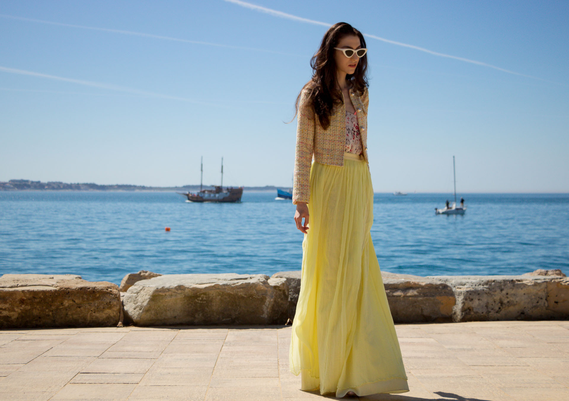 Veronika Lipar Fashion Blogger of Brunette from Wall Street wearing maxi yellow tulle skirt from Needle & Thread, short yellow tweed jacket from Storets, floral silk top, blush Gianvito Rossi plexi pumps, white shoulder bag, Le specs white cat eye sunglasses by the sea